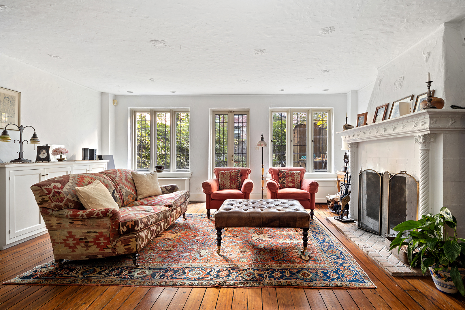 A living area with several windows, hardwood floors, a couch, and a fireplace with a mantel.