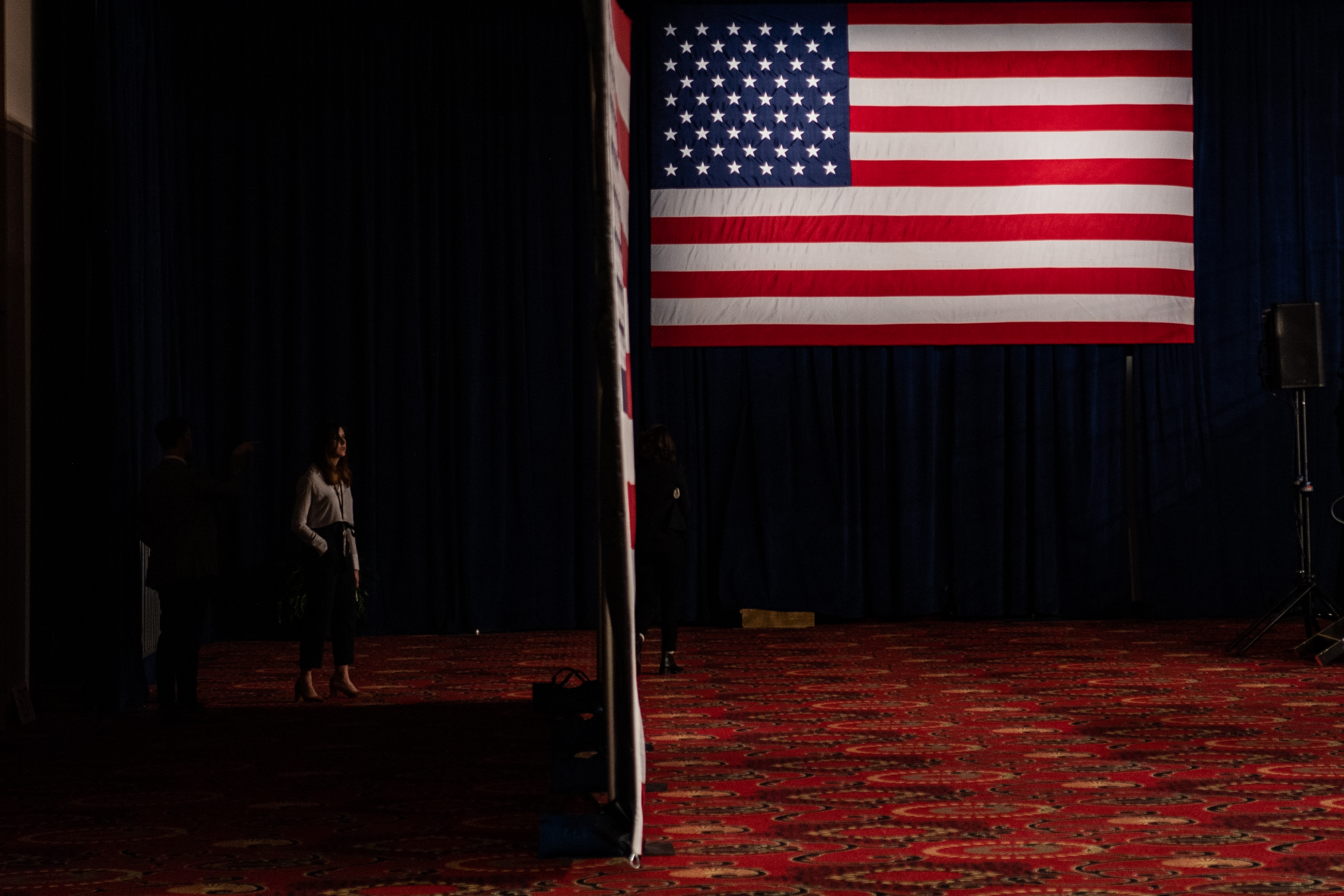 A staffer stands in the shadow ahead of the Bernie Sanders caucus night celebration in Des Moines, Iowa.