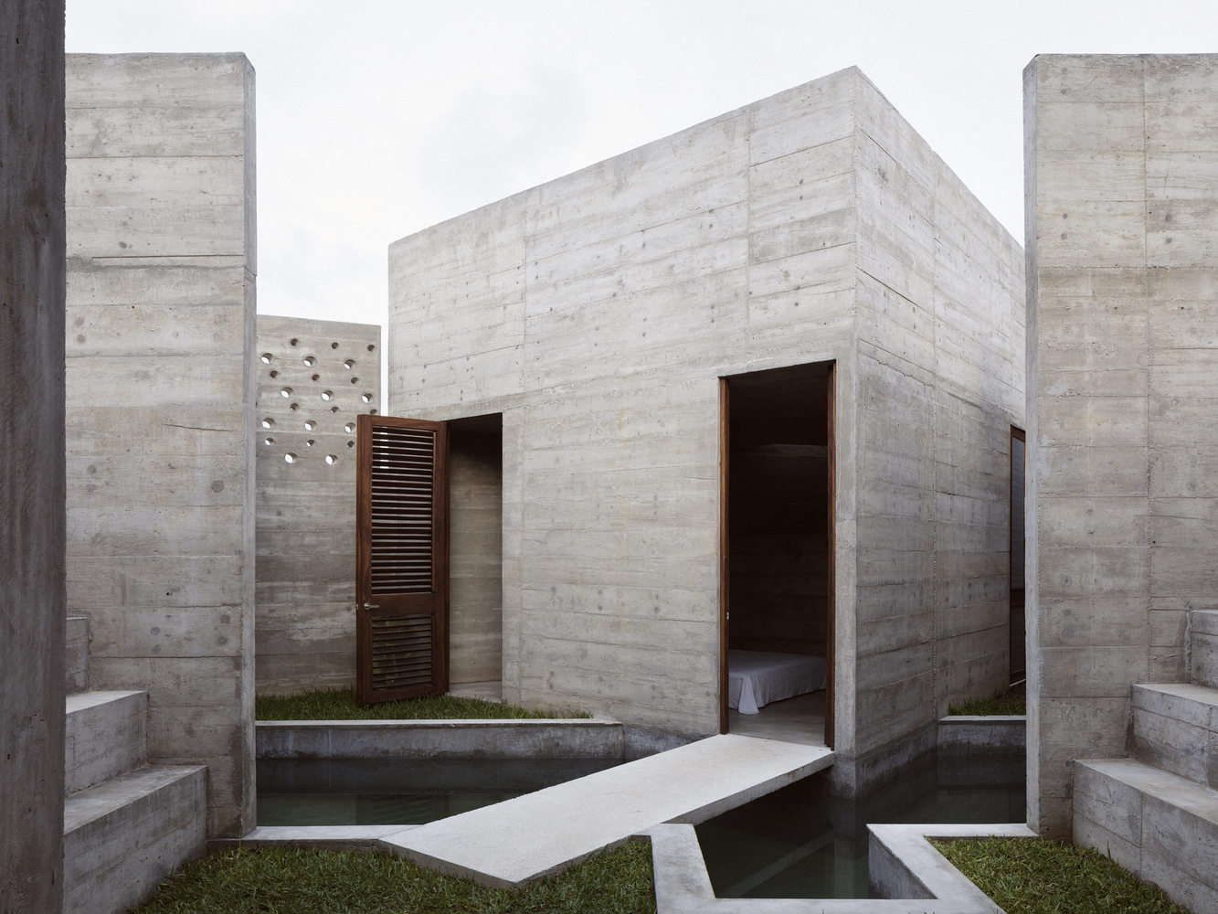 Concrete house with narrow concrete walkway in a courtyard.