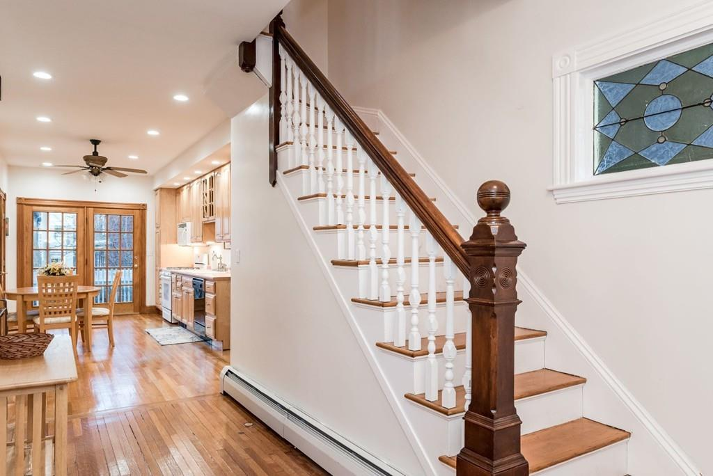 The entryway of a shiny Victorian house, with the stairwell featuring prominently.