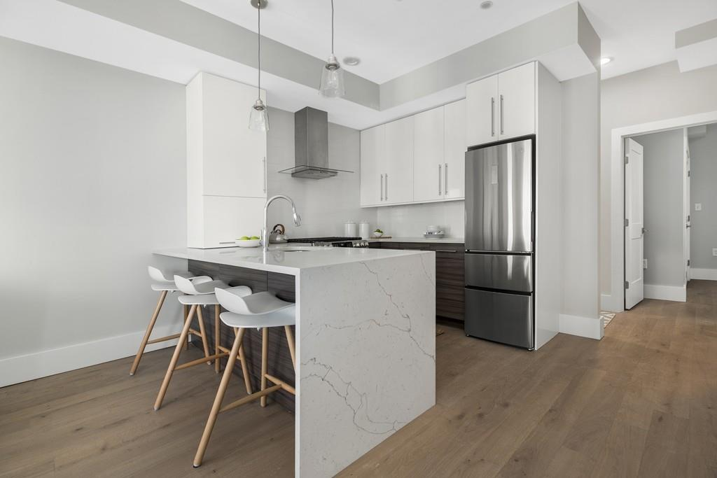 An open modern kitchen with stools in front of the main counter.