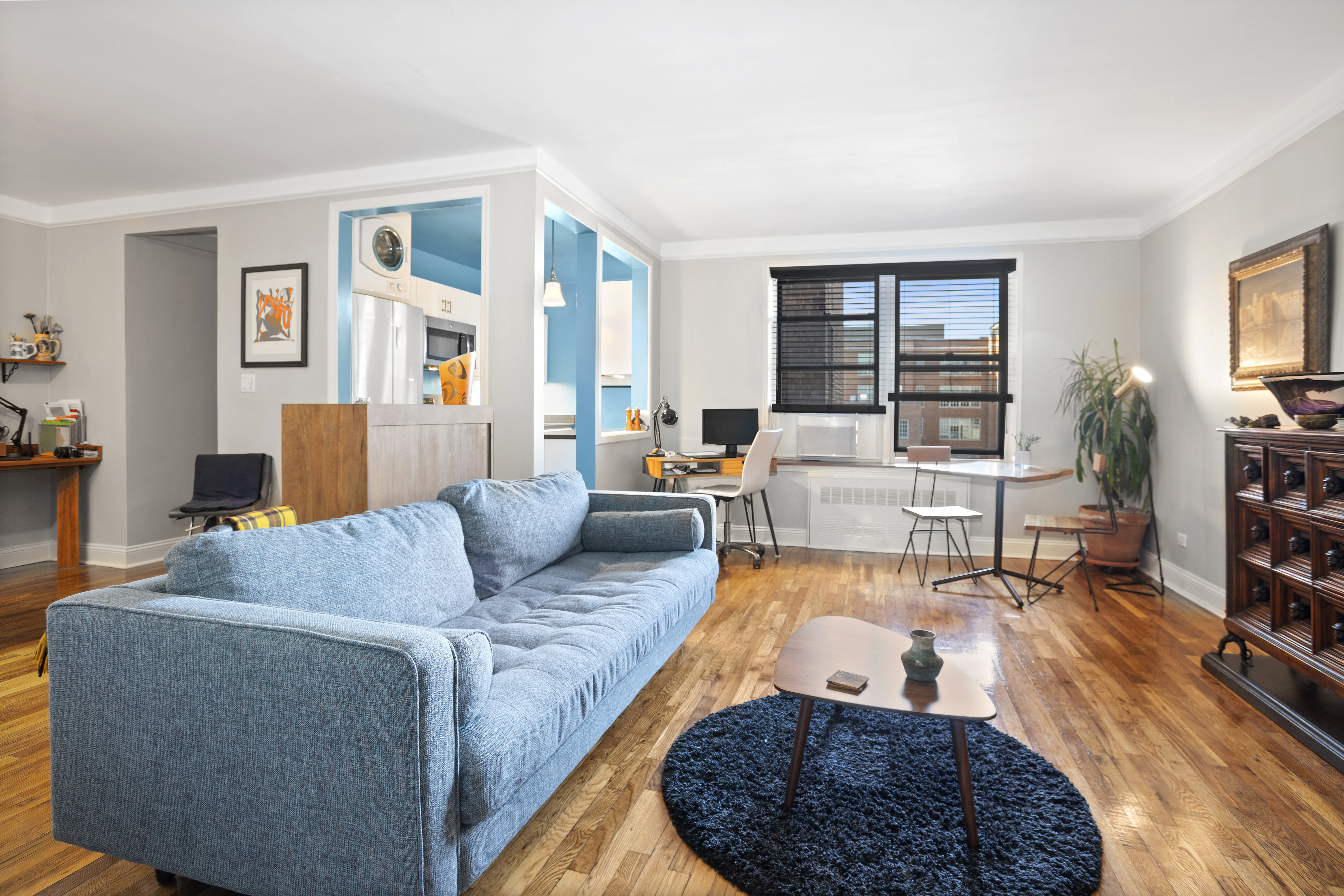 A living room with hardwood floors, a blue couch, white walls, a dark blue rug, and a small wood coffee table.