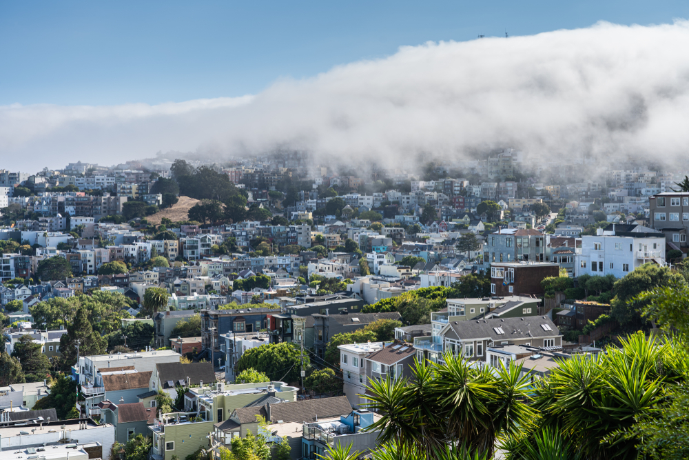 Fog rolling in from the right side of the photo over rows of colorful houses.