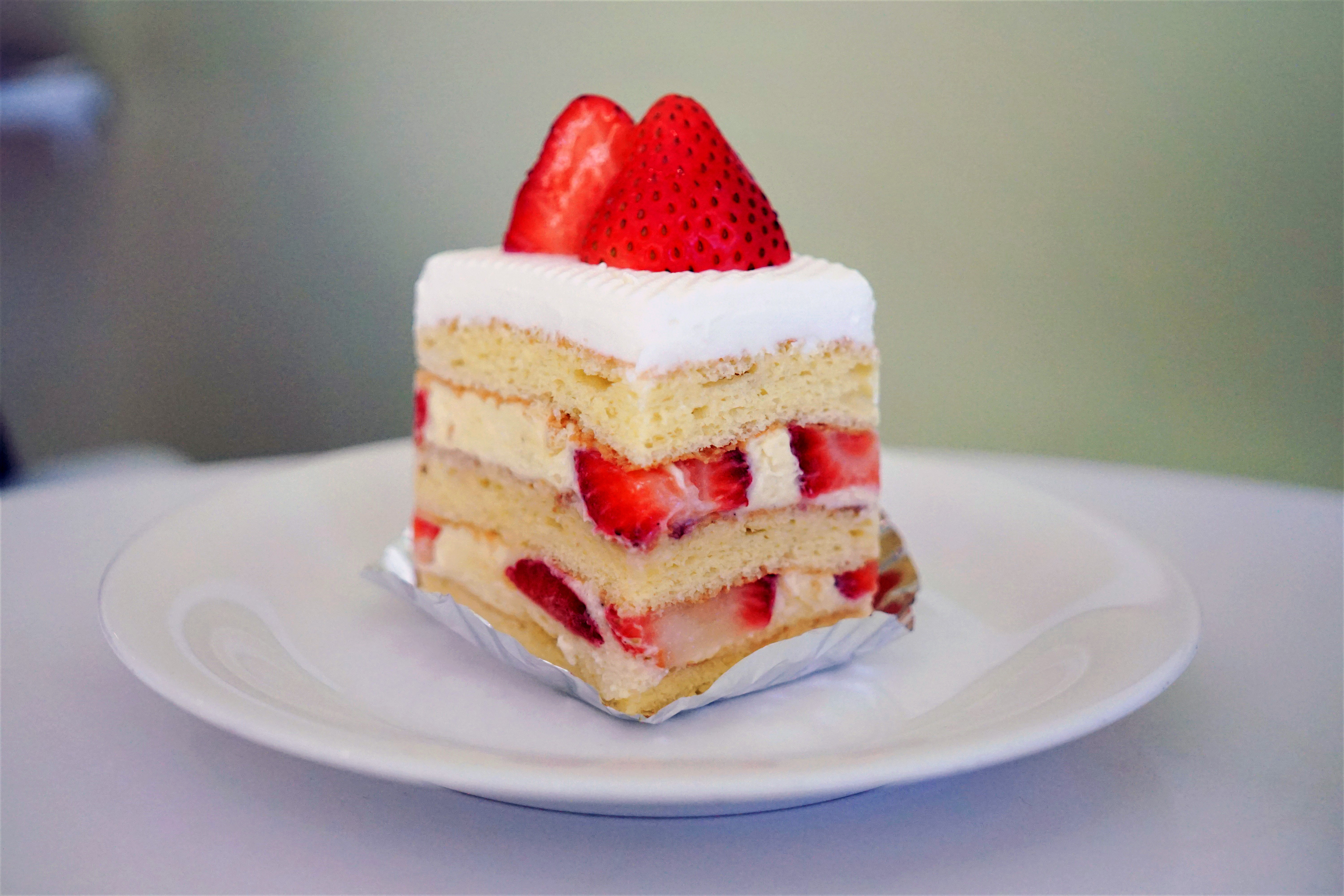 A slice of cake with layers of strawberries and cream and a strawberry on top.