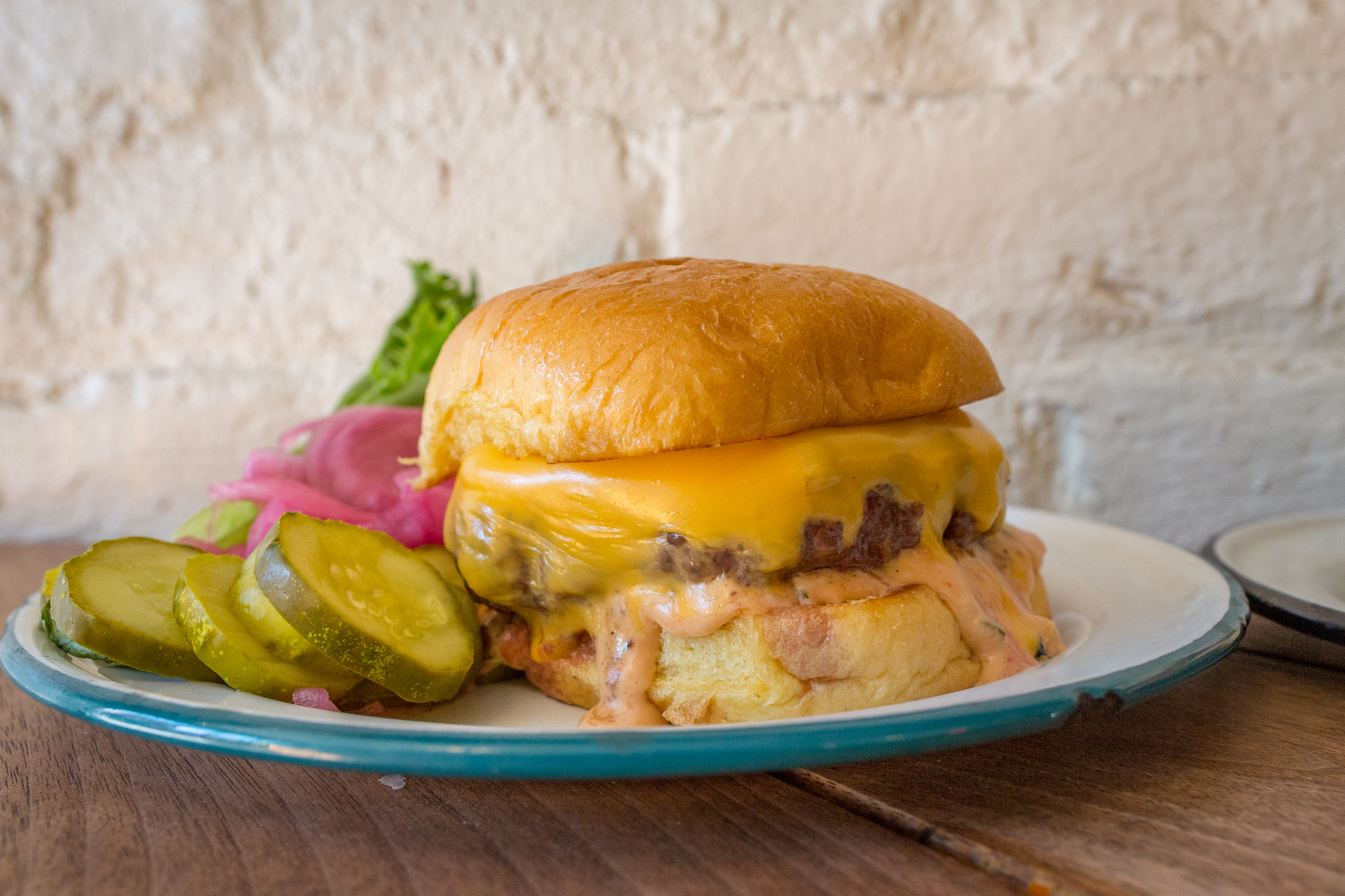 A white plate with a blue outline with a burger on top that's covered in cheese. Sliced pickles sit on the side of the plate