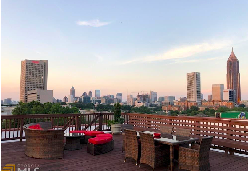 A rooftop with a big city's sky rises in the distance, beneath a blue sky.