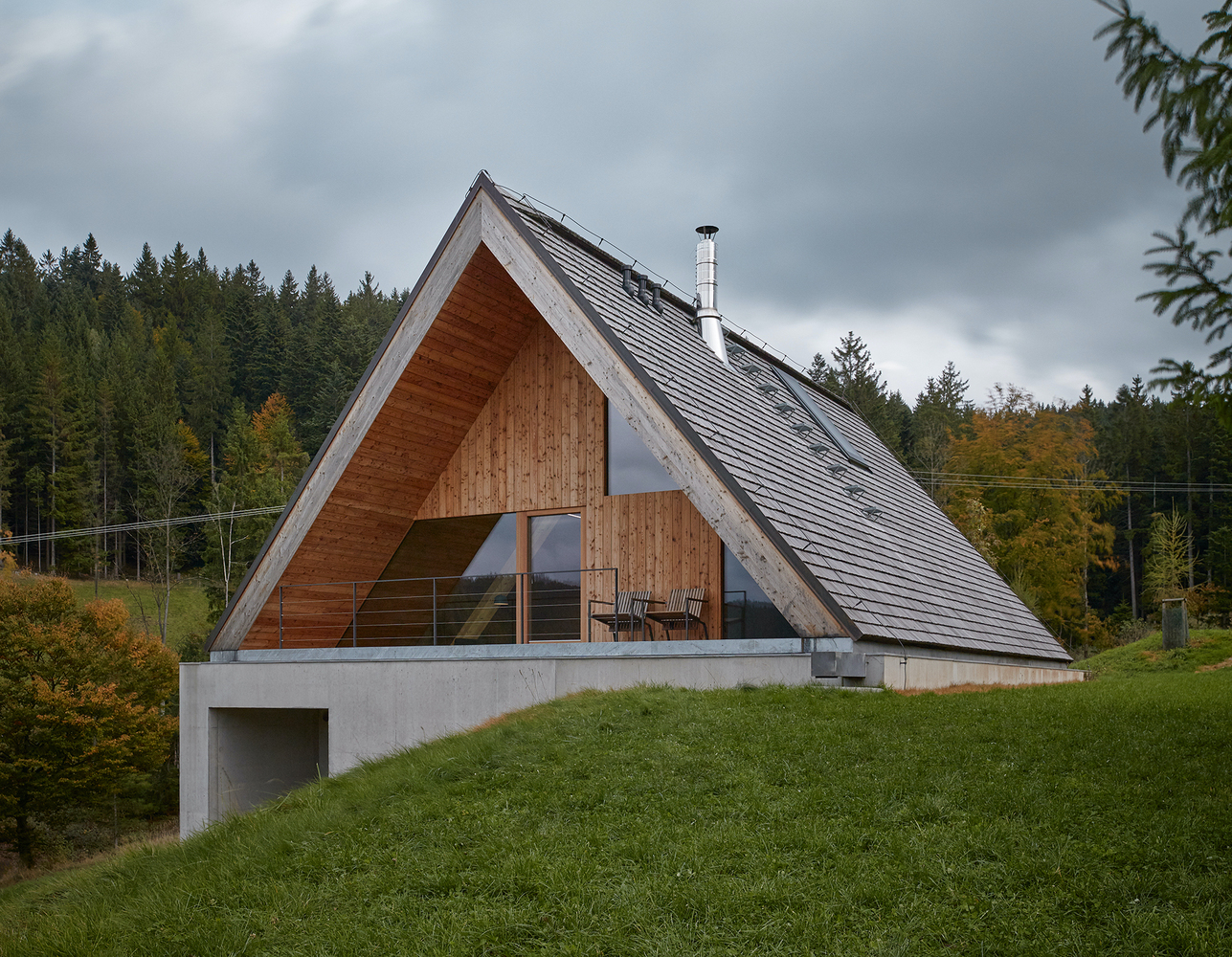 A-frame house with wood facade sits on a concrete base.