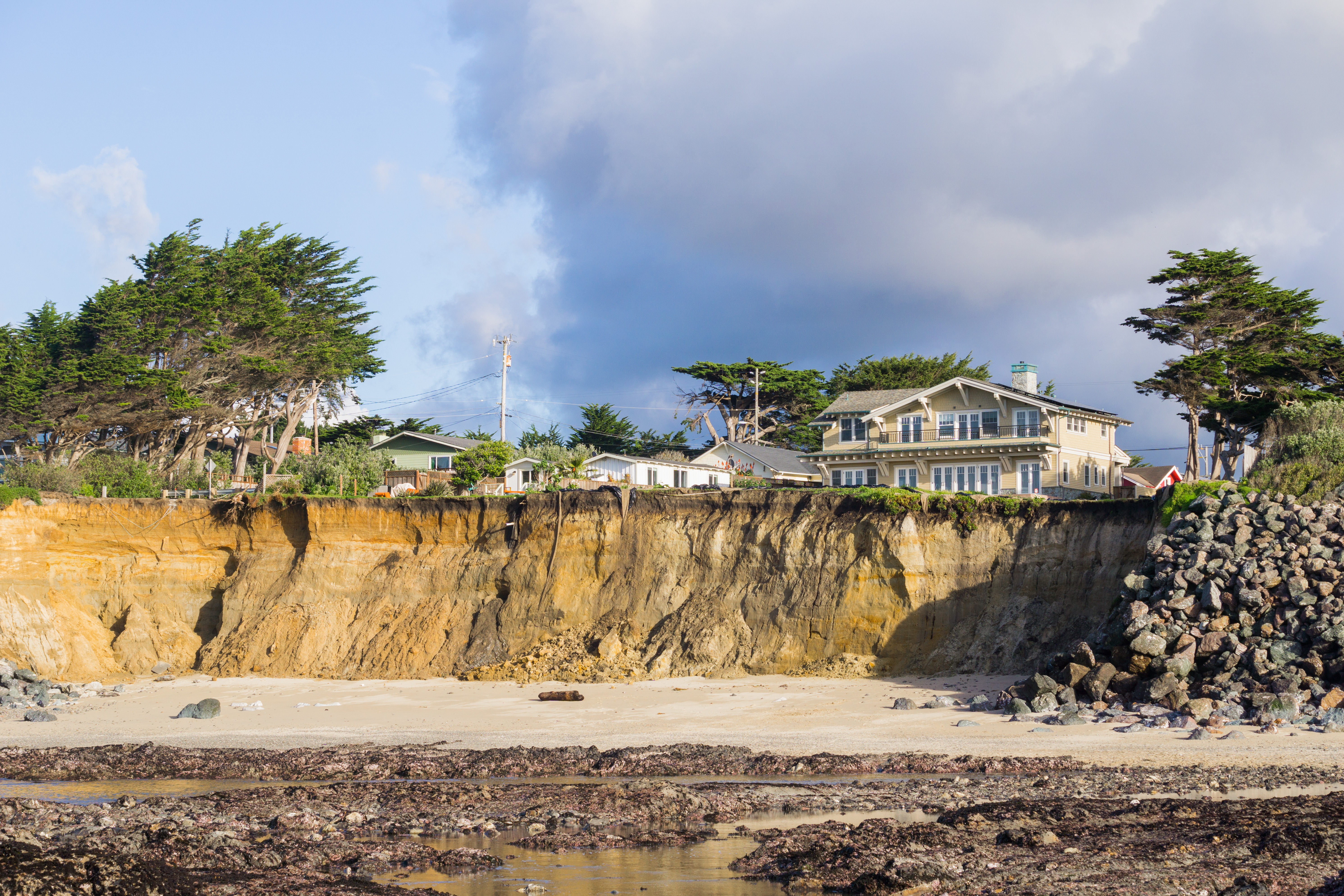 A beach with a cliff and a home on top.