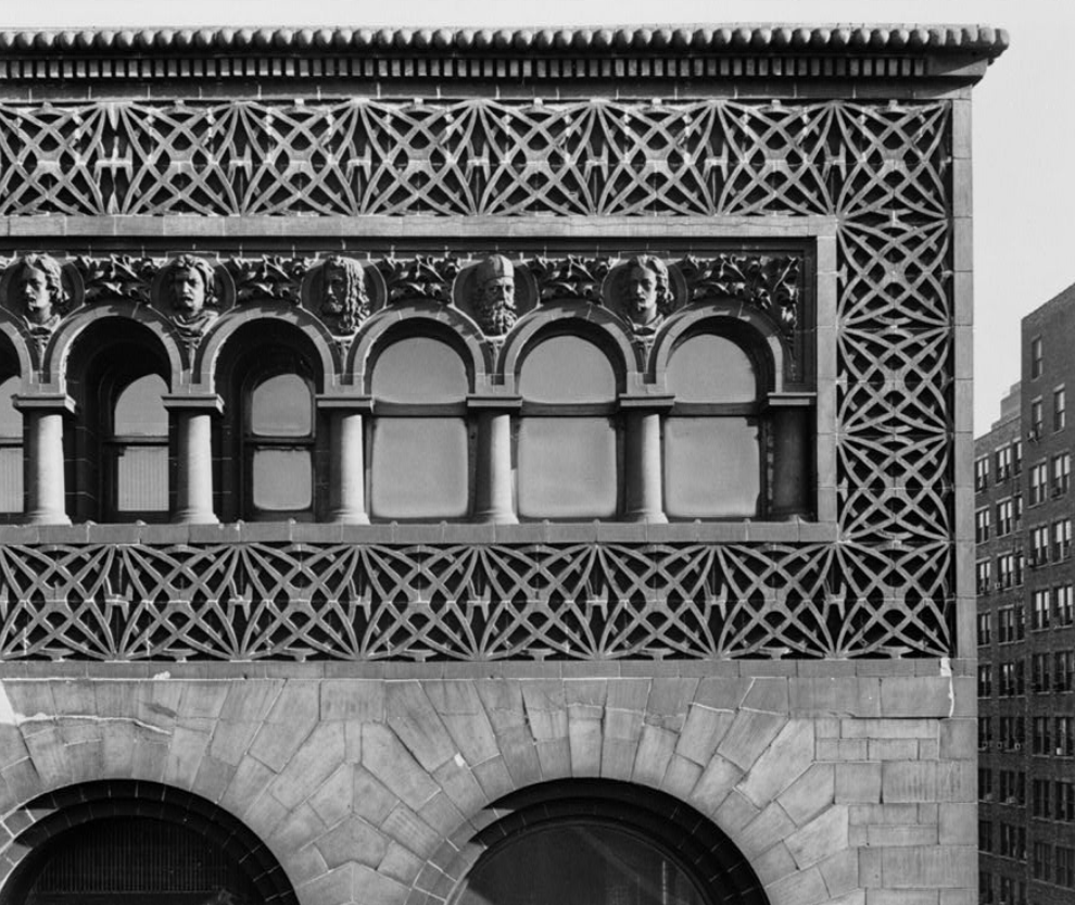 A black and white photograph showing detailed stonework around arched windows with carved busts between each column.