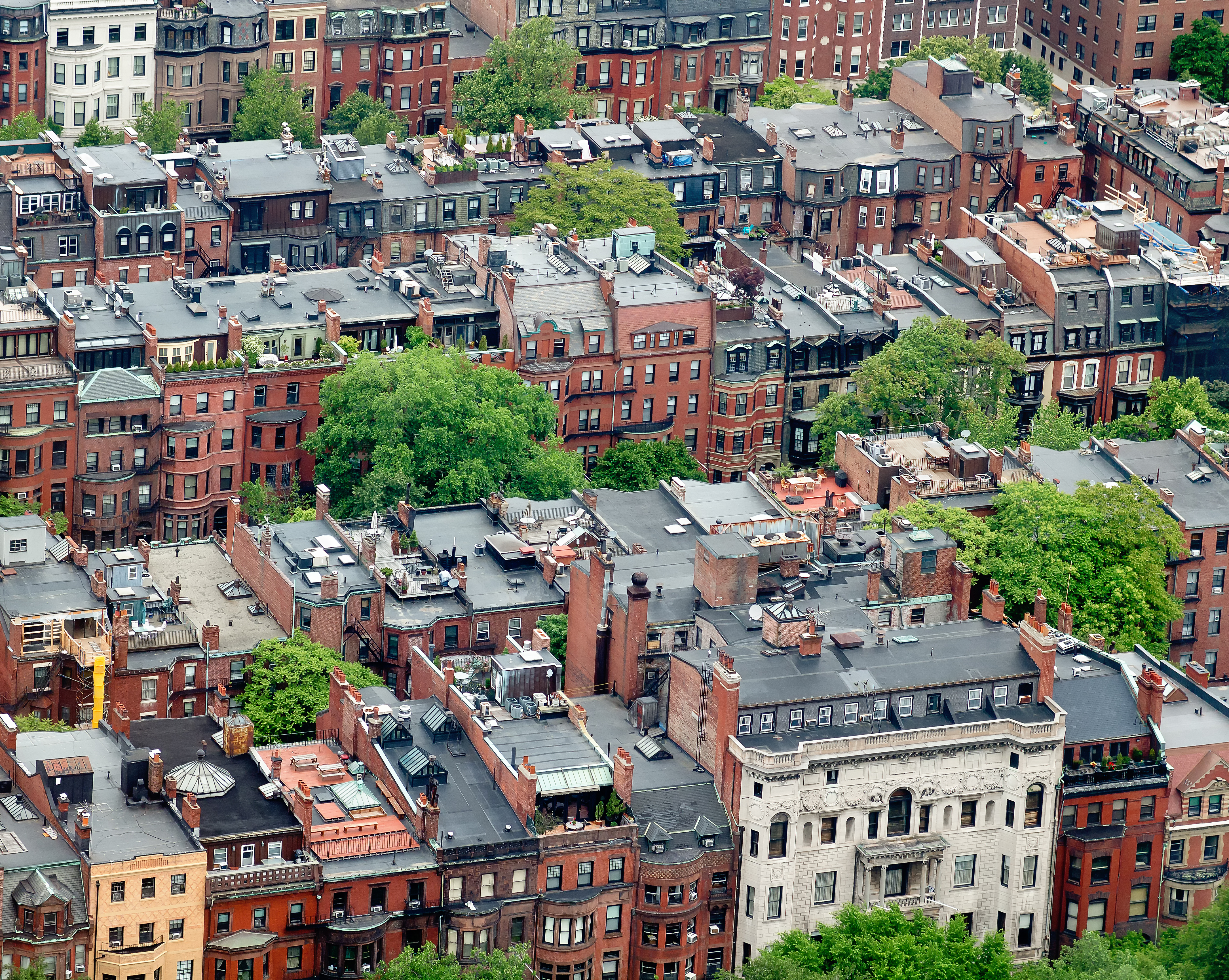 Aerial view of rows of small apartment buildings in a city.