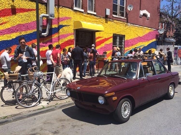 A crowd of people stands in front of a brightly painted wall with bikes and a red car visible in the street