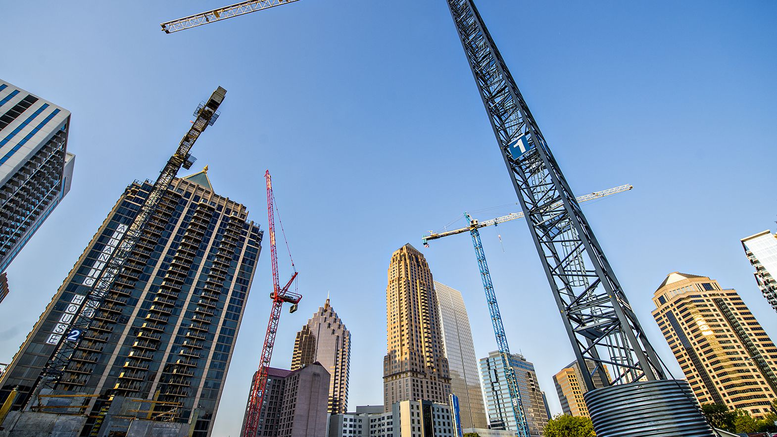 Cranes and skyscrapers build up a city with a blue sky behind it.