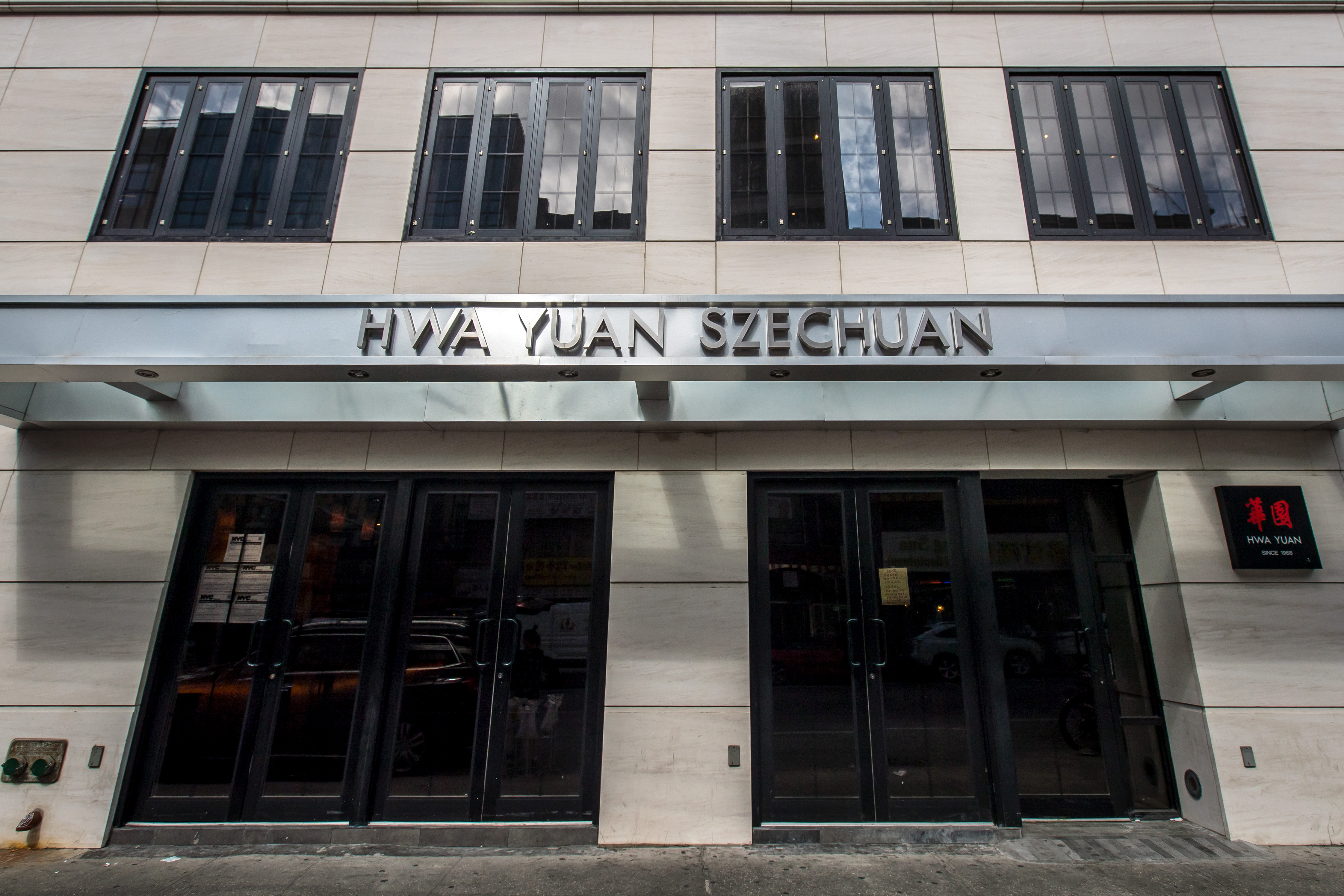 An exterior photo of Sichuan restaurant Hwa Yuan which shows a white stone exterior and a silver sign that bears the name.