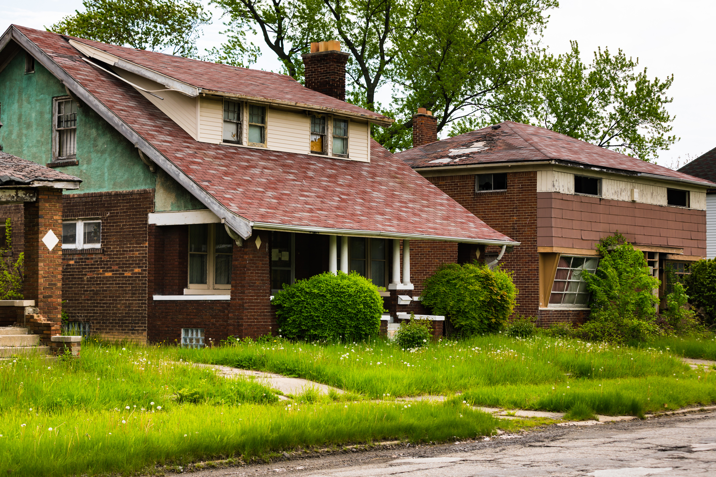Two abandoned homes. They both have missing or boarded up windows and uncut front yards.