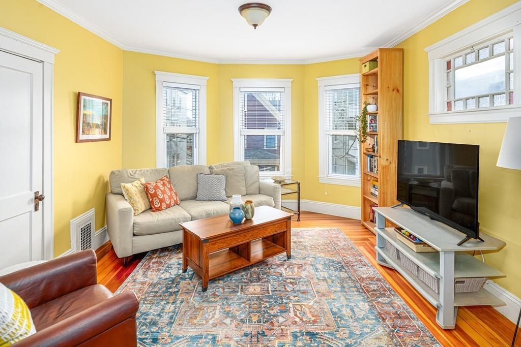A cozy living room with a couch and a chair and a TV as well as a bay window.
