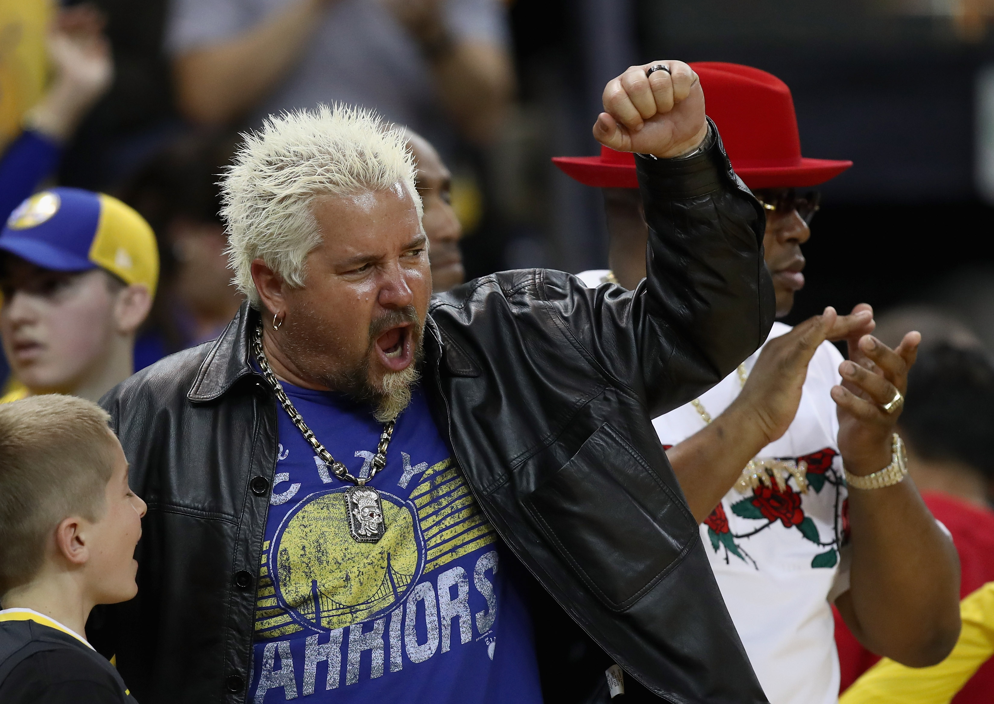 Guy Fieri in a Golden State Warriors t-shirt, gold chain, and black leather jacket, pumps his fist while sitting courtside at an NBA basketball game.