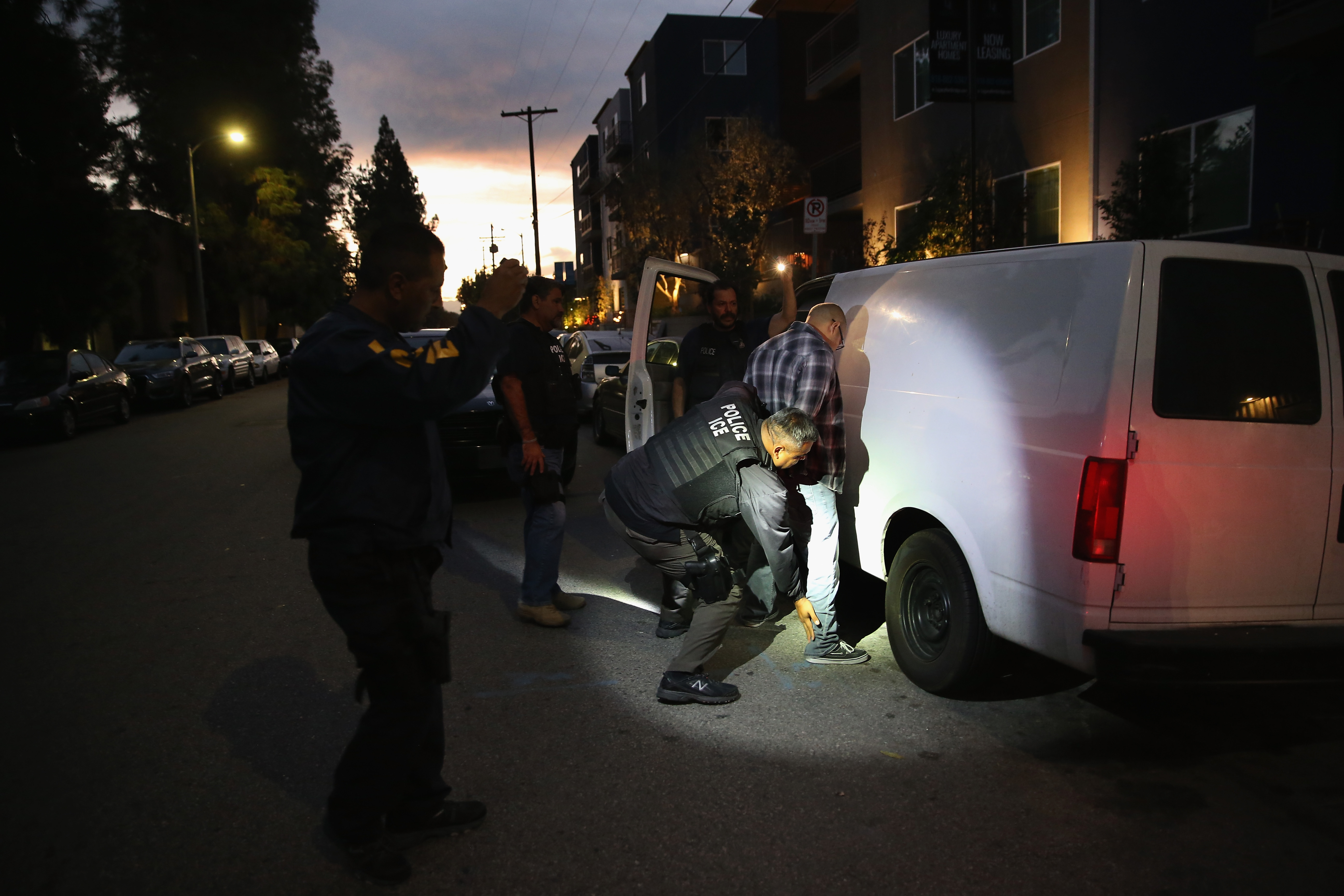 An ICE agent shines a flashlight on a man beside a van parked on a residential street while the other agent arrests the man.