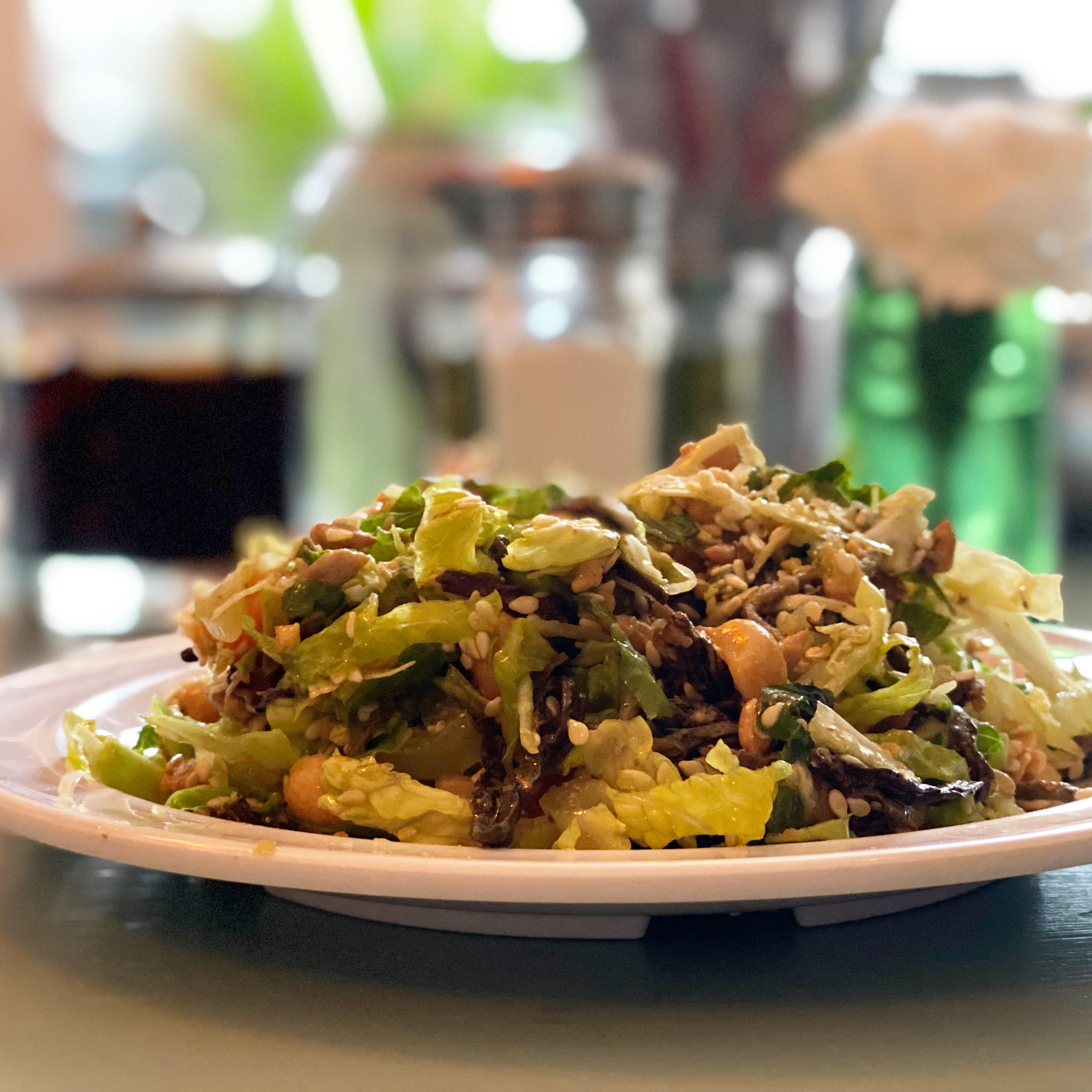 A white plate loaded with cabbage, tomatoes, peanuts, and sesame seeds looks like a pile of green, with pops of brown from the fried garlic and dark splotches of fermented tea leaves