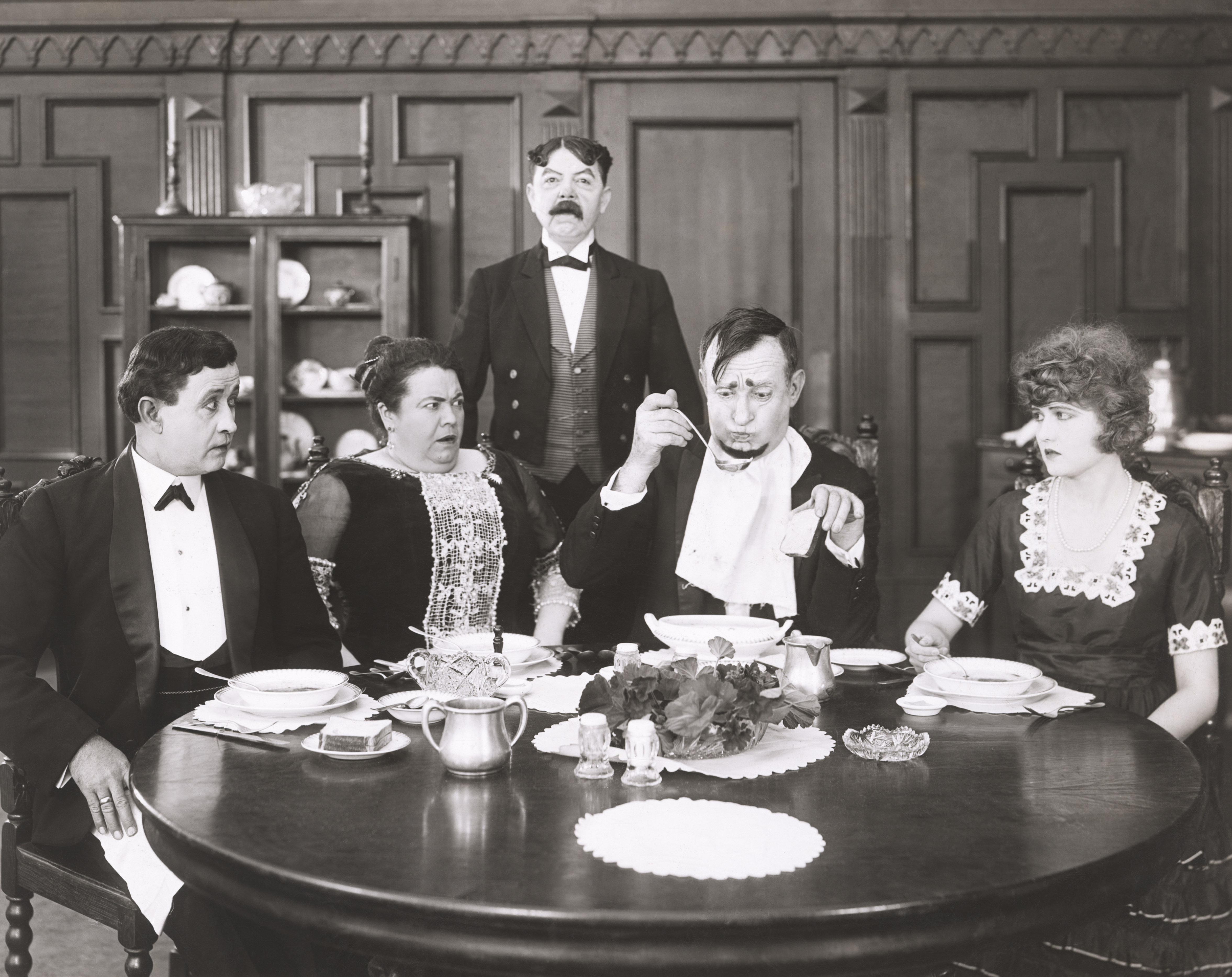 Man taking a bite of food at the dinner table with a worried look on his face as other table guests look on