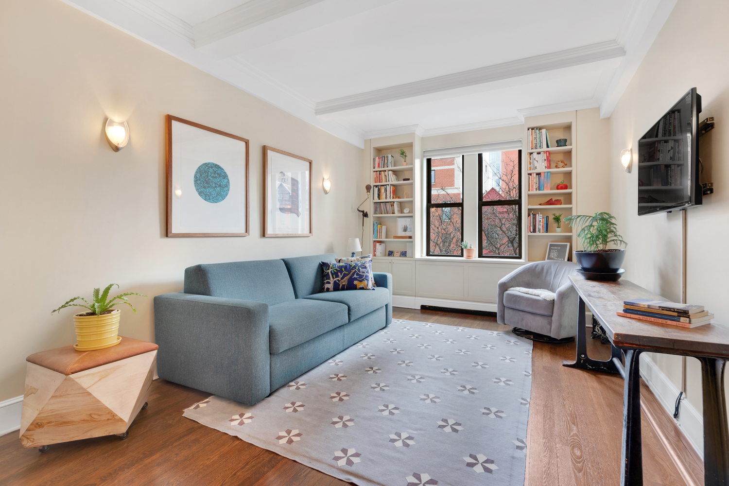 A living area with hardwood floors, two windows, a blue couch, and a rug.