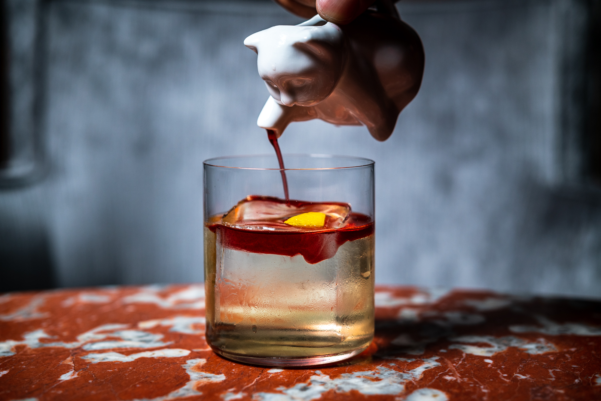 A white cat container is used to pour red chokeberry syrup into a translucent Bases Loaded cocktail at Silver Lyan