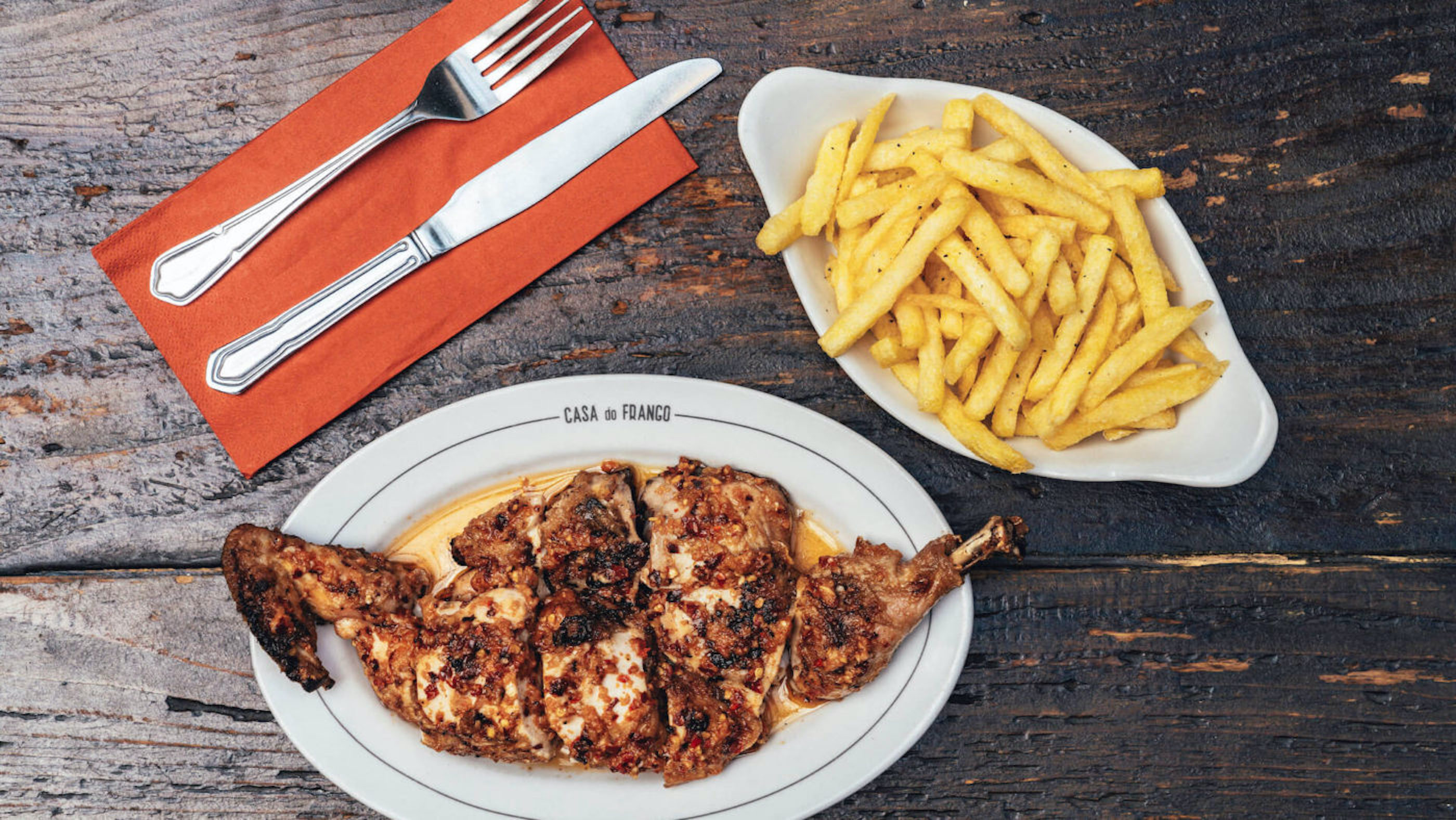 Piri piri chicken on a white platter with chips on a white platter, with cutlery on a red napkin