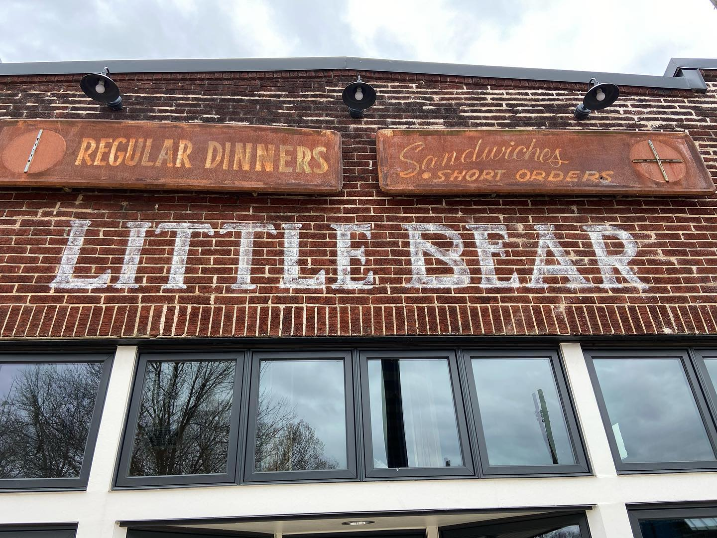 "The handpainted sign for Little Bear with original, rusted signs above reading ""Regular Dinners"", ""Sandwiches, Short Orders"""