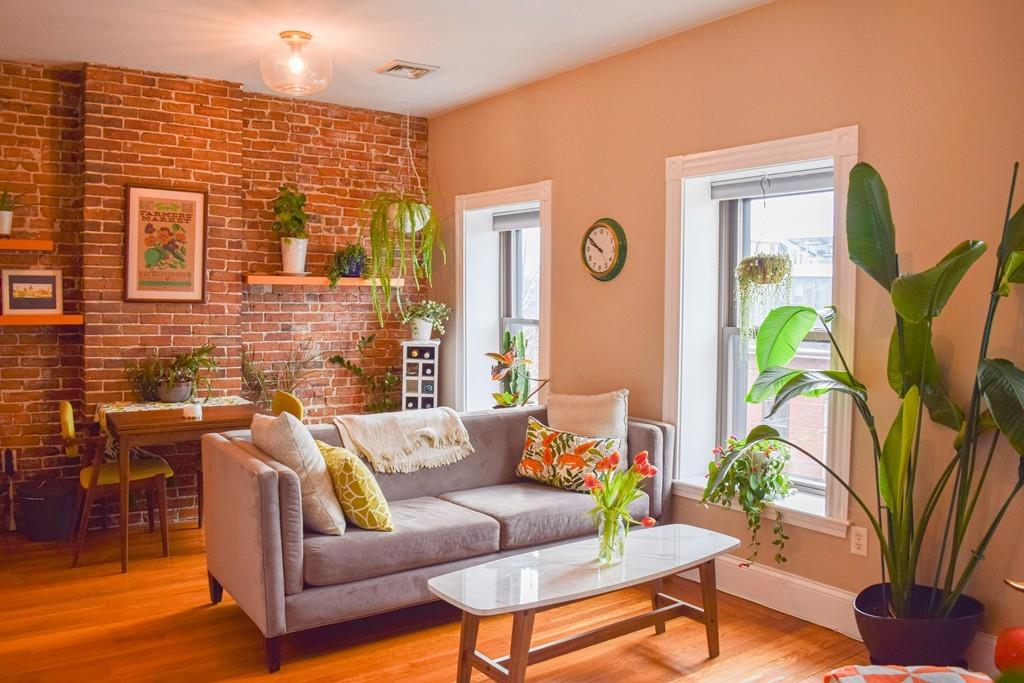 A living room with furniture and a large plant and plenty of exposed brick.