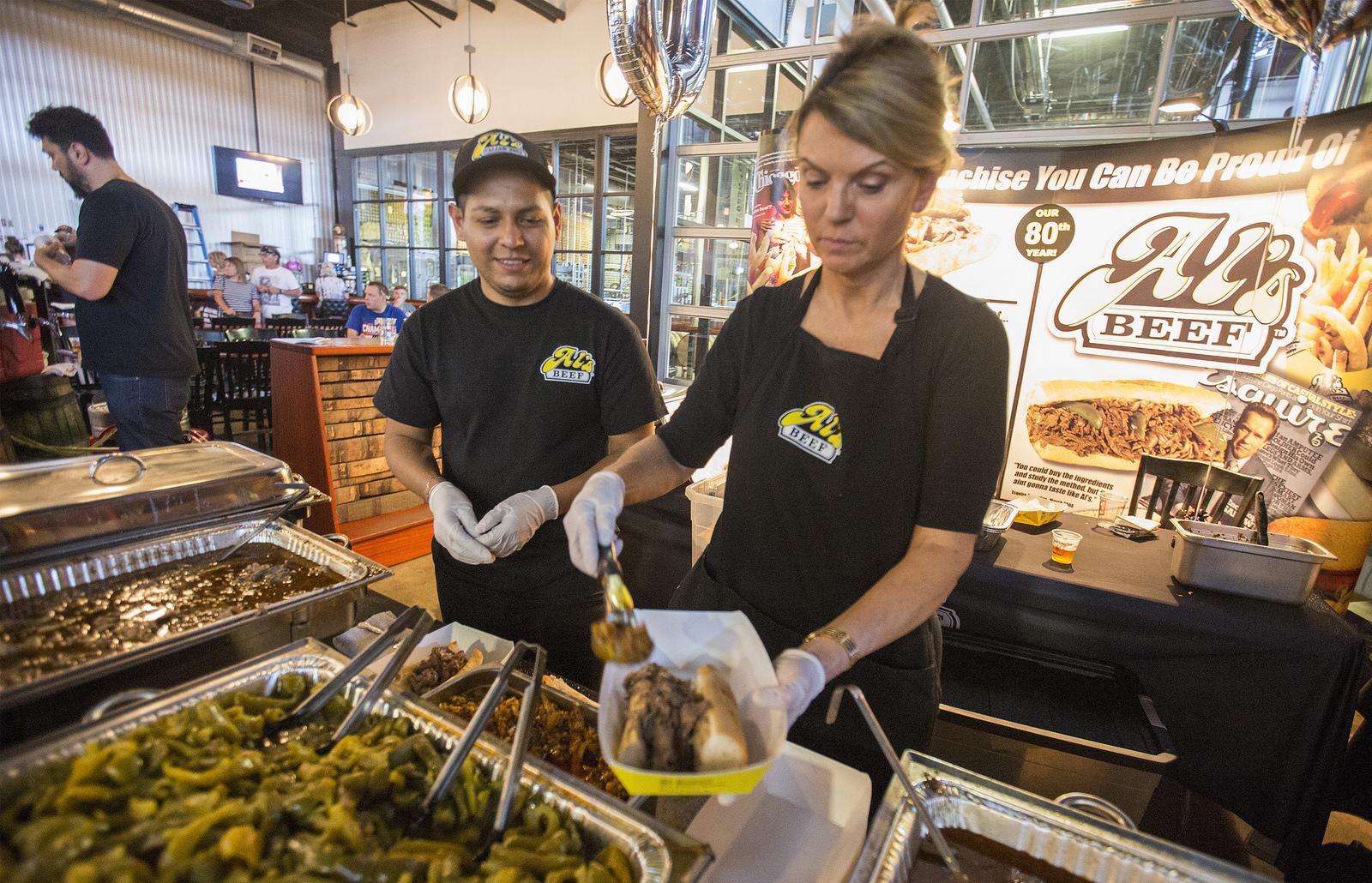 A woman serving an Italian beef sandwich