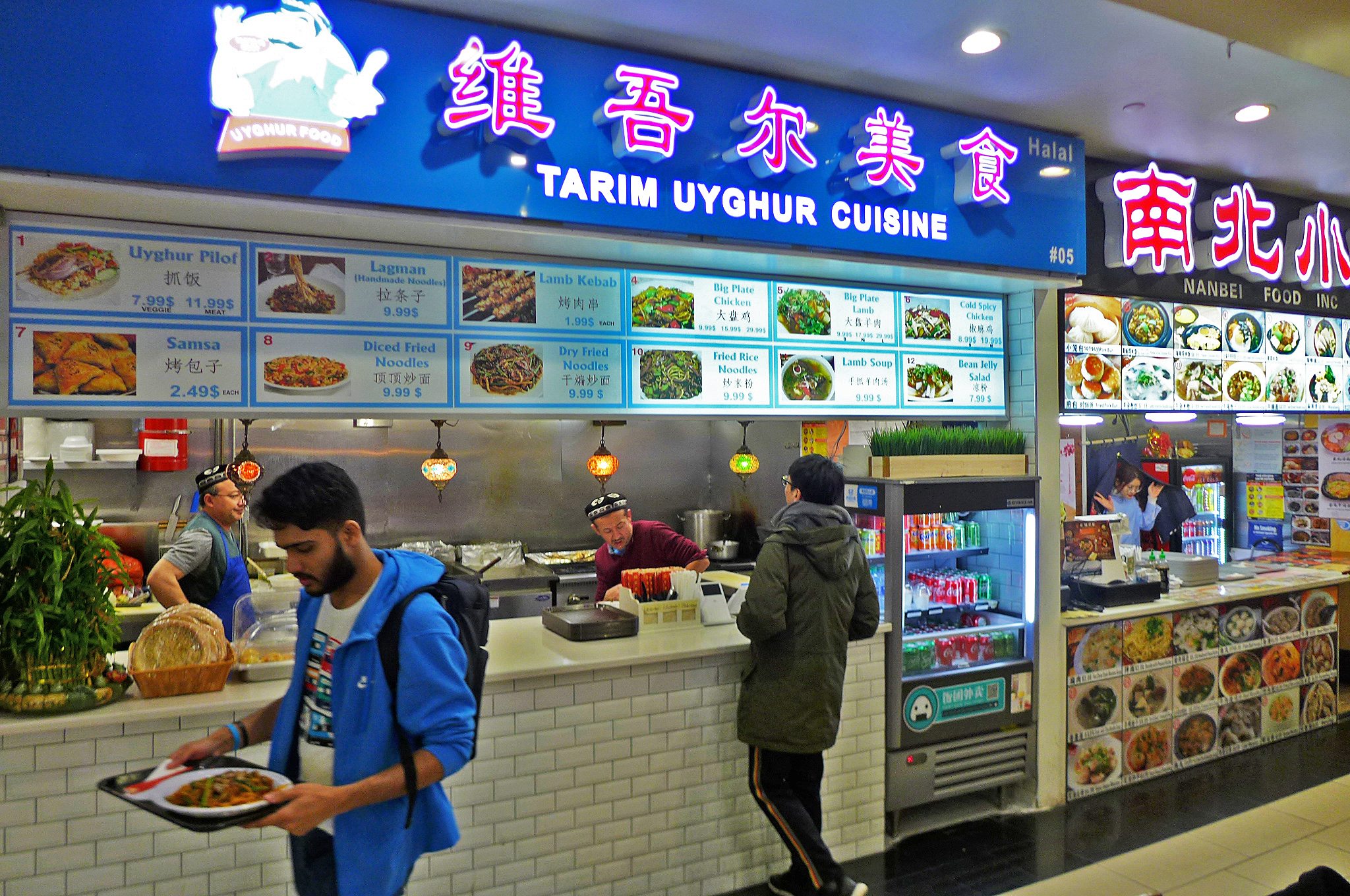 A food court stall with a blue marquee, with a couple of customers in front.