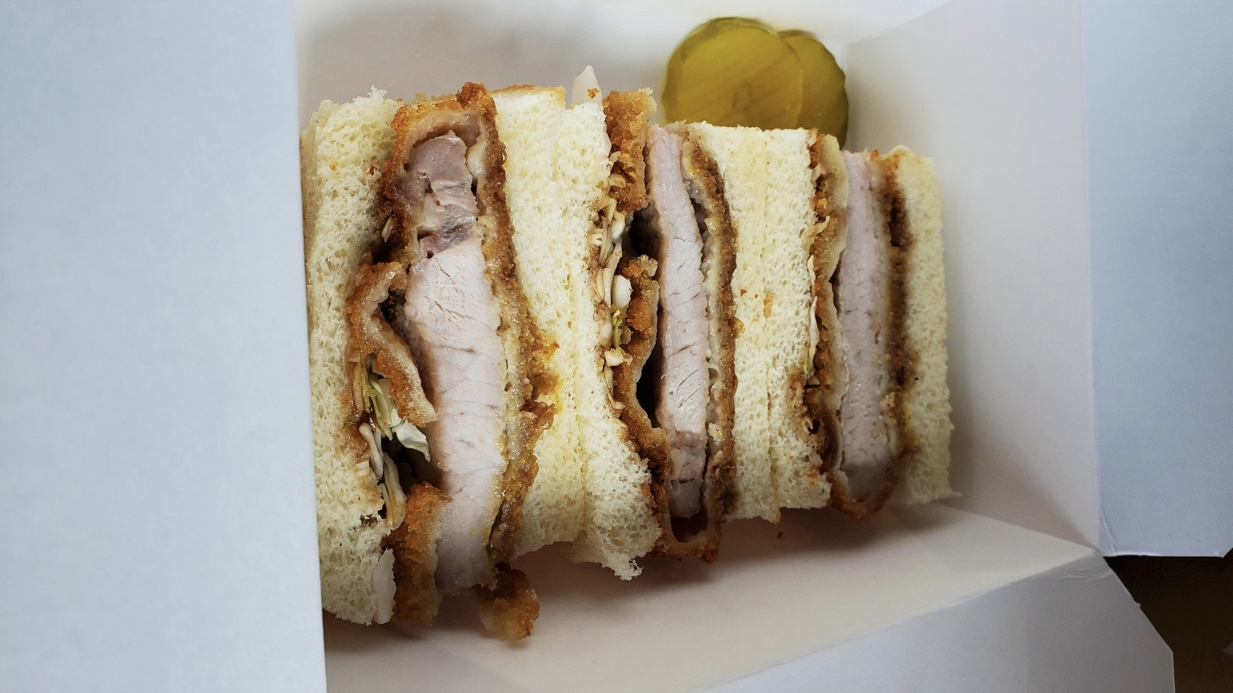 A picture of a sandwich, cut in half, with hunks of fried pork in the middle
