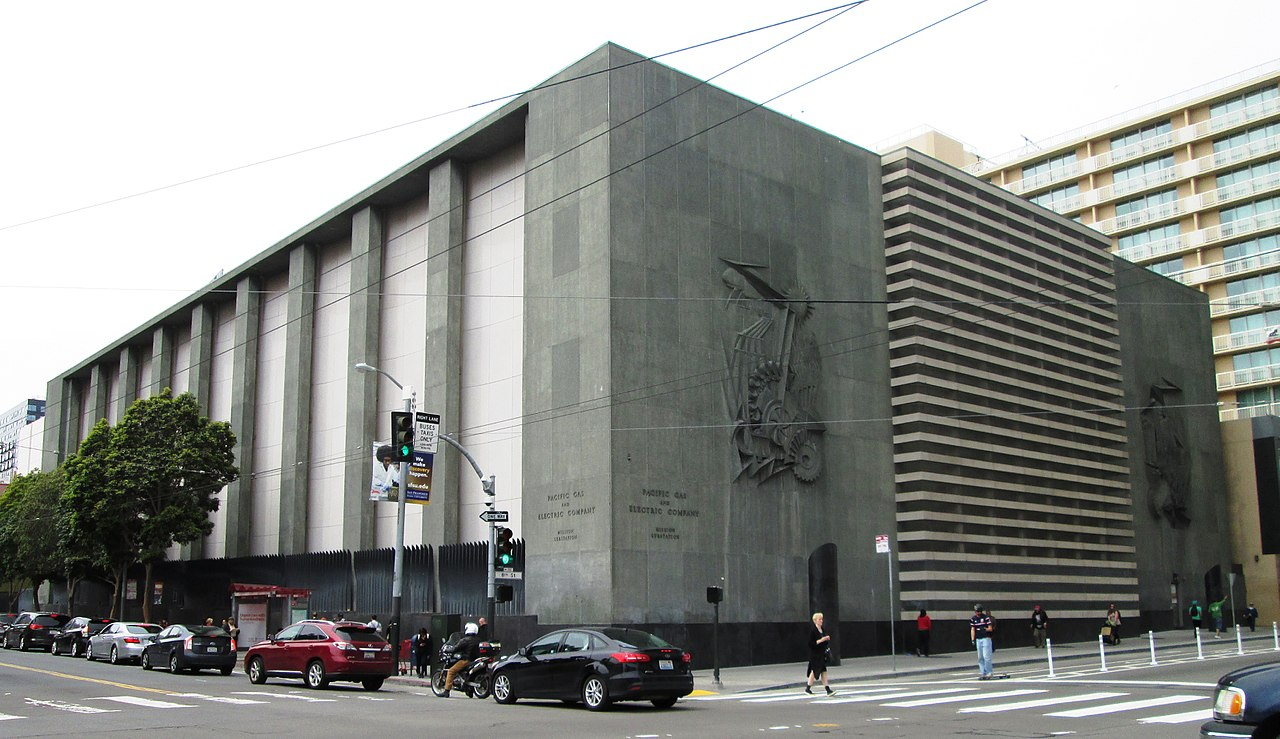 A massive corner substation building, a low, gray cement building behind a black fence.
