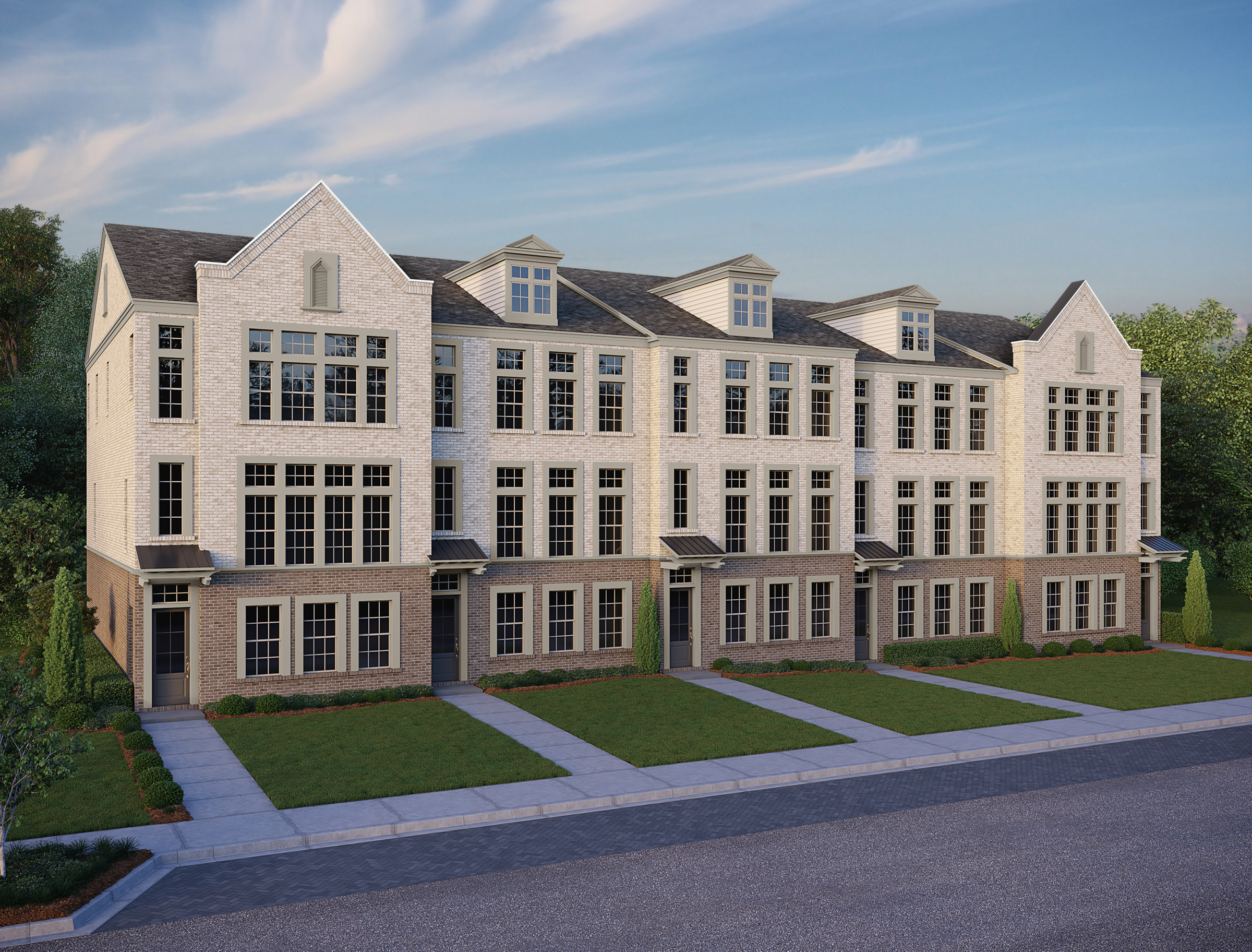 A large white brick townhome project with three stories, walkways, and a bank of green trees behind it.