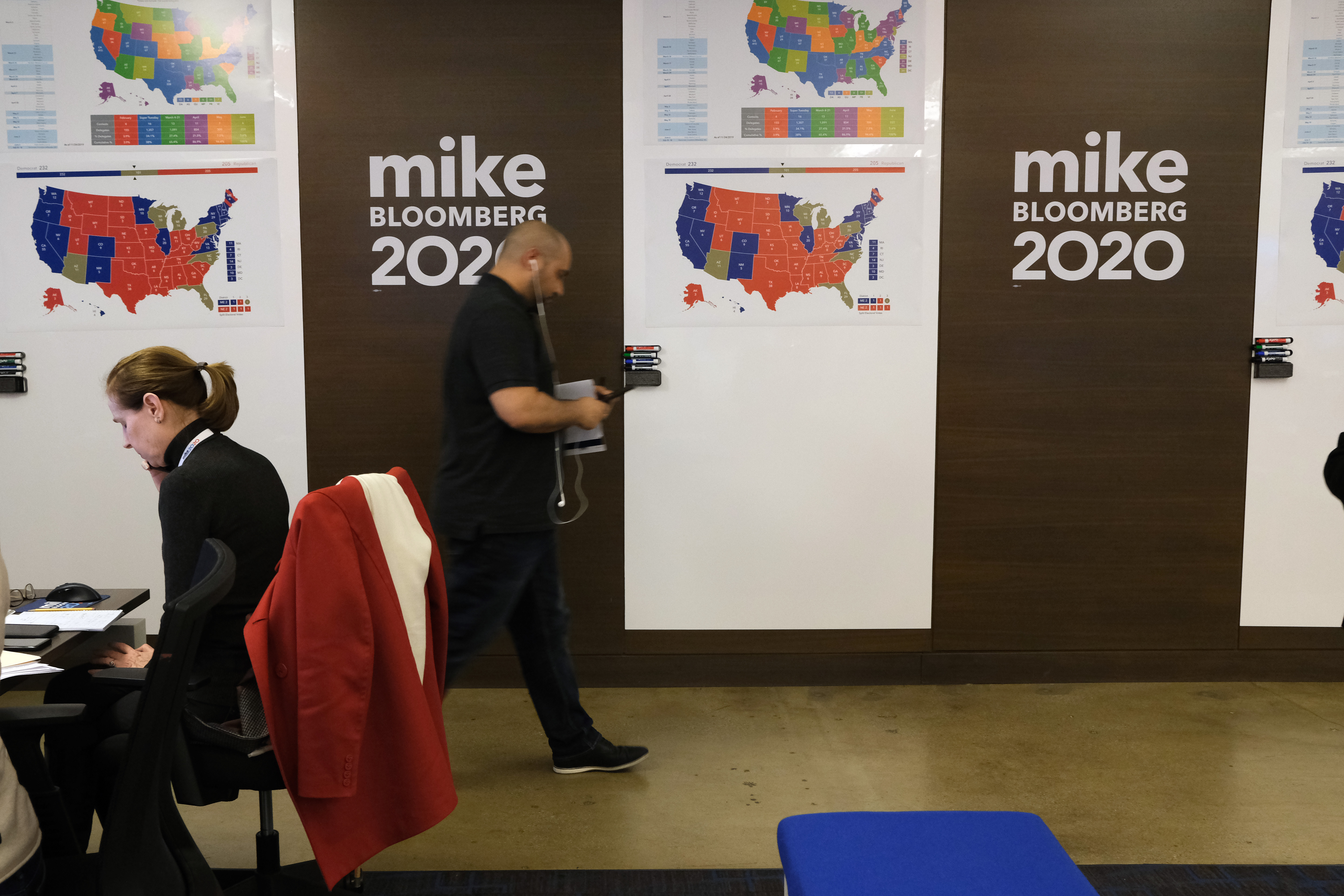 Staffers walk around the headquarters of Mike Bloomberg's campaign.