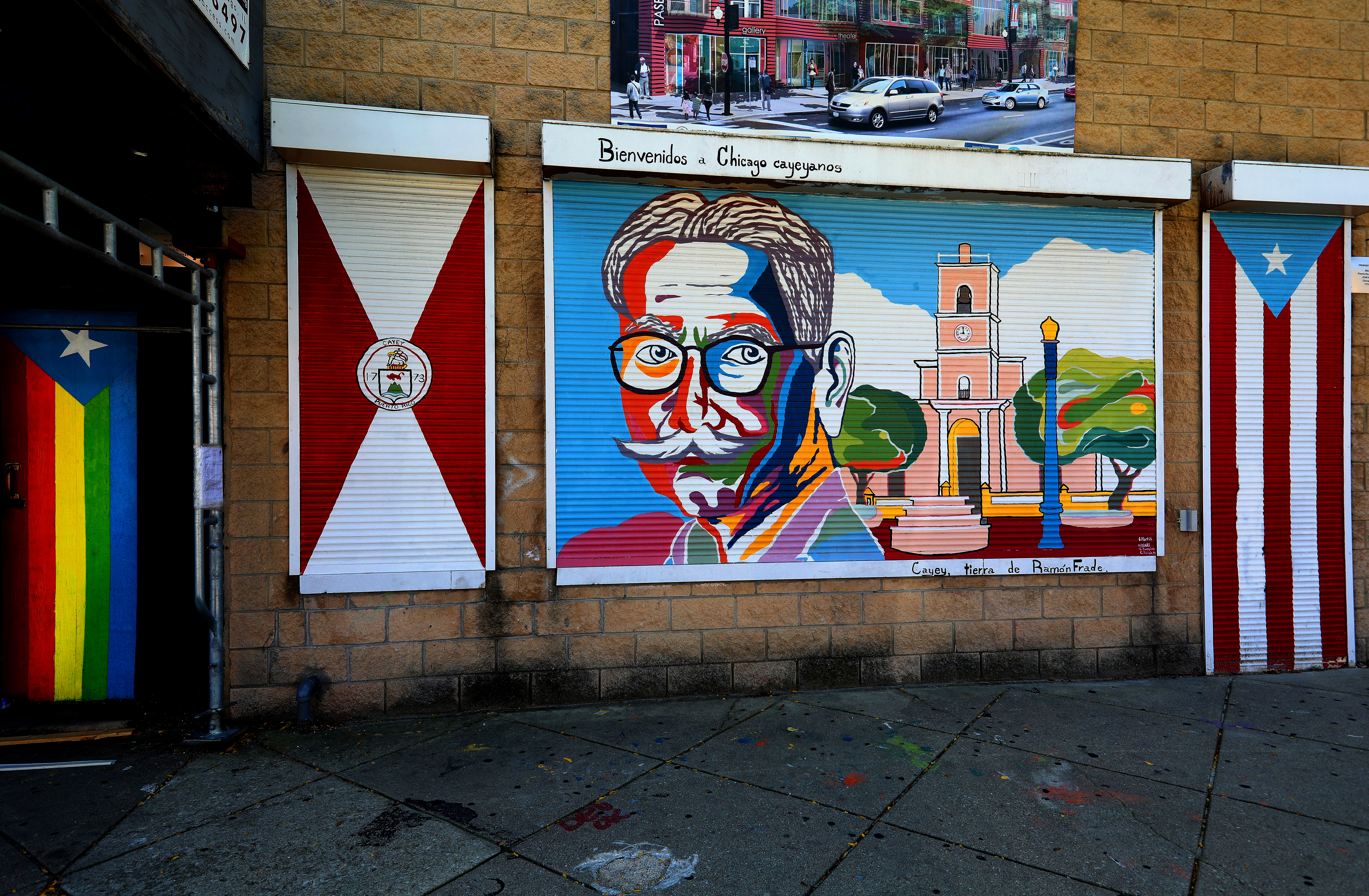 Colorful murals painted on the side of a building - a mans face with many colors included, a building, and a Puerto Rican flag.