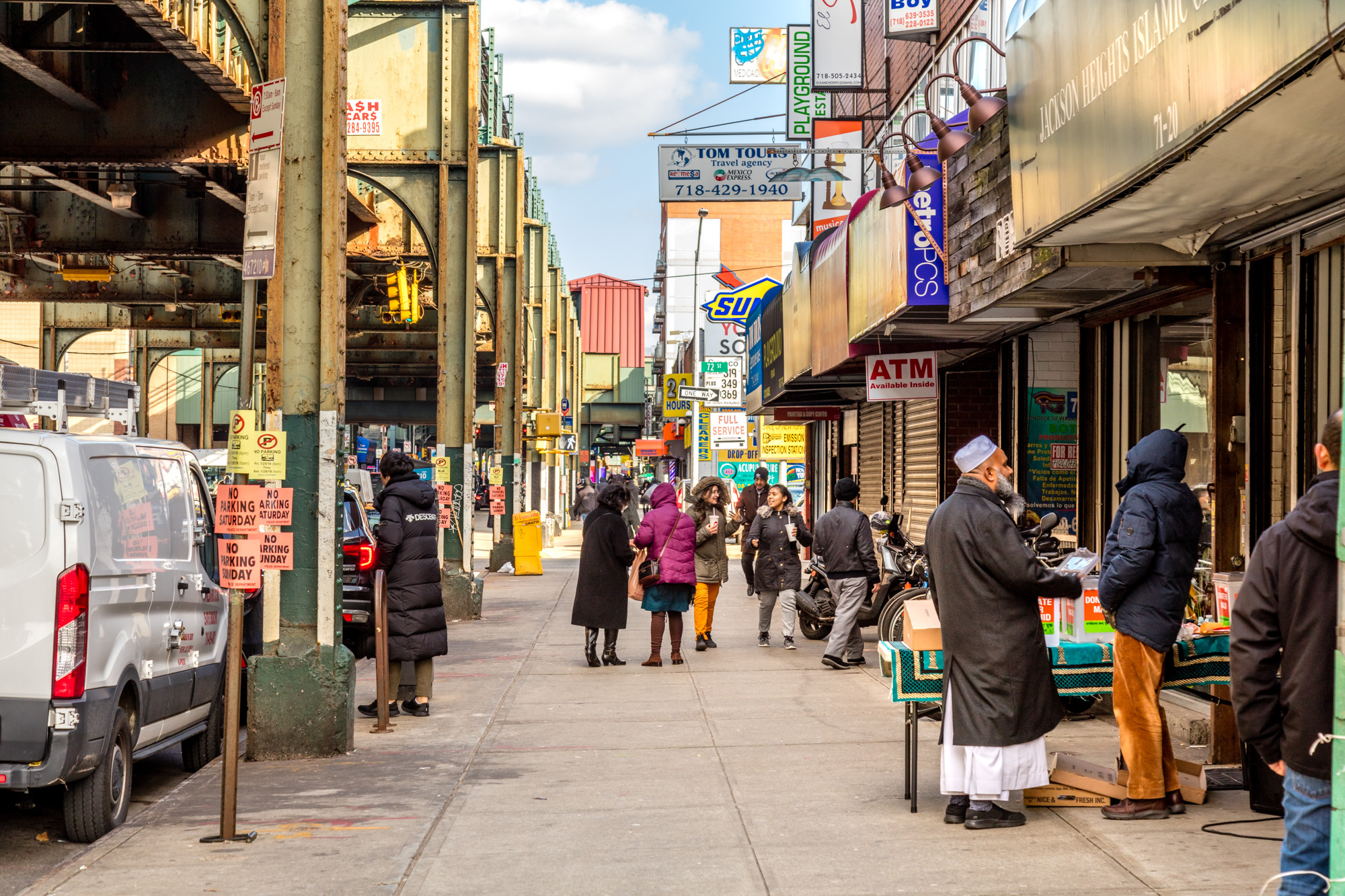 Busy sidewalk in Jackson Heights, Queens - many people on the street, two men talking, women walking on the sidewalk - busy block of shops on the right, and the elevated above ground subway on the left.