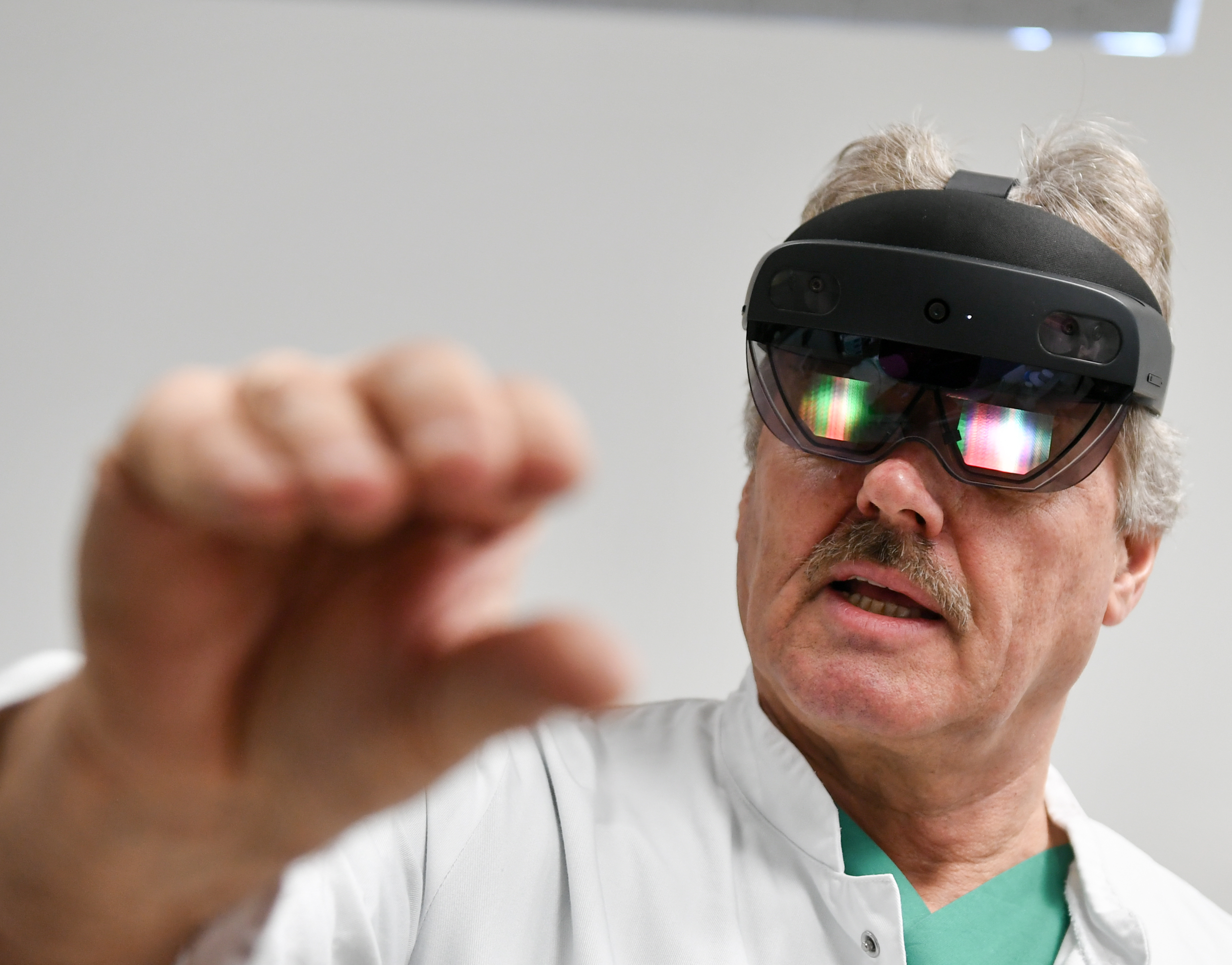 A man wearing a virtual reality headset reaches a hand toward the viewer.