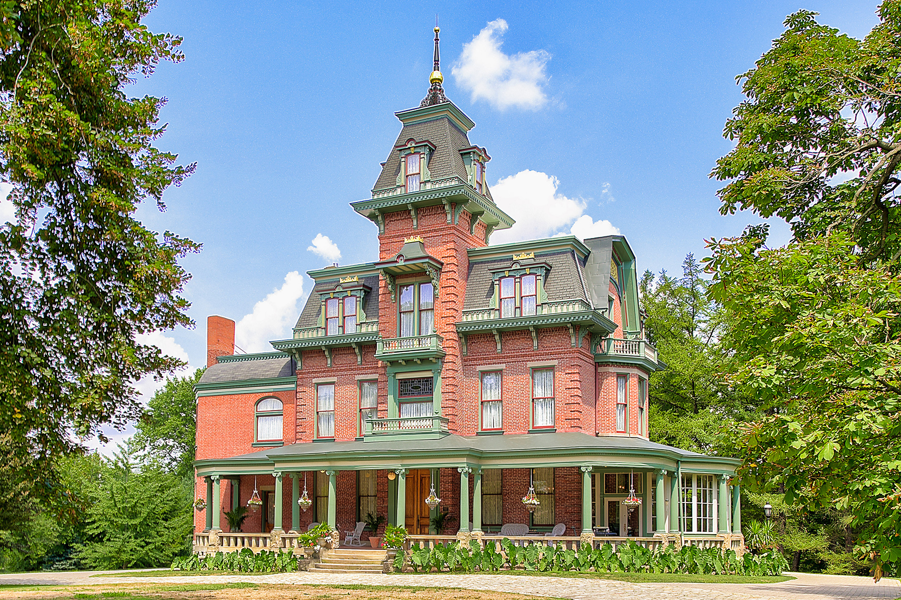 A large red brick Victorian house with green trim that's surrounded by green trees. The house features a large wrap-around porch and a turret in the center.