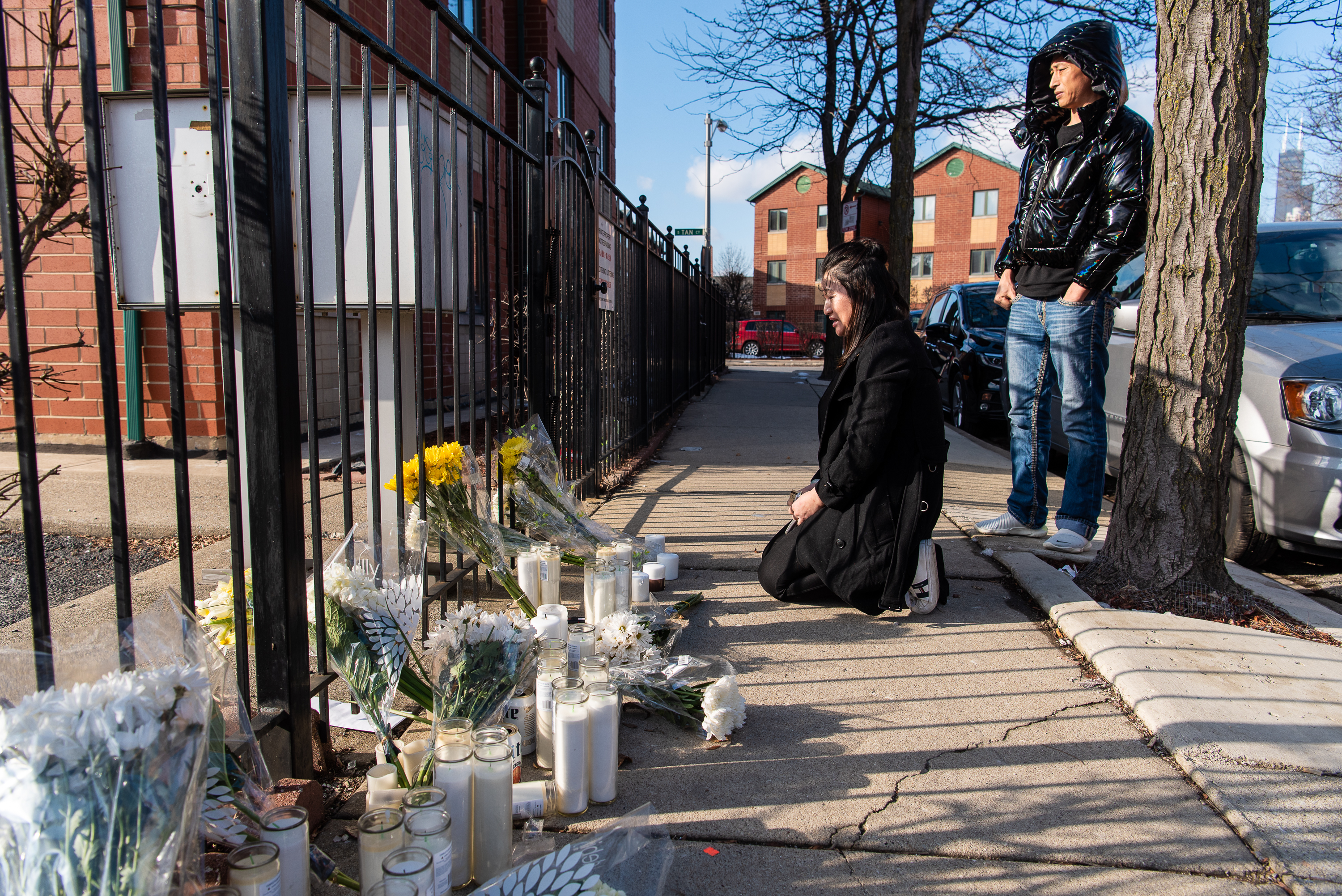 A young woman breaks down in front of a vigil that sits outside the apartment complex where Huayi Bian and Weizhong Xiong were murdered, Tuesday, Feb. 11, 2020, in Chicago. Bian and Xiong were murdered in an armed robbery Sunday morning.
