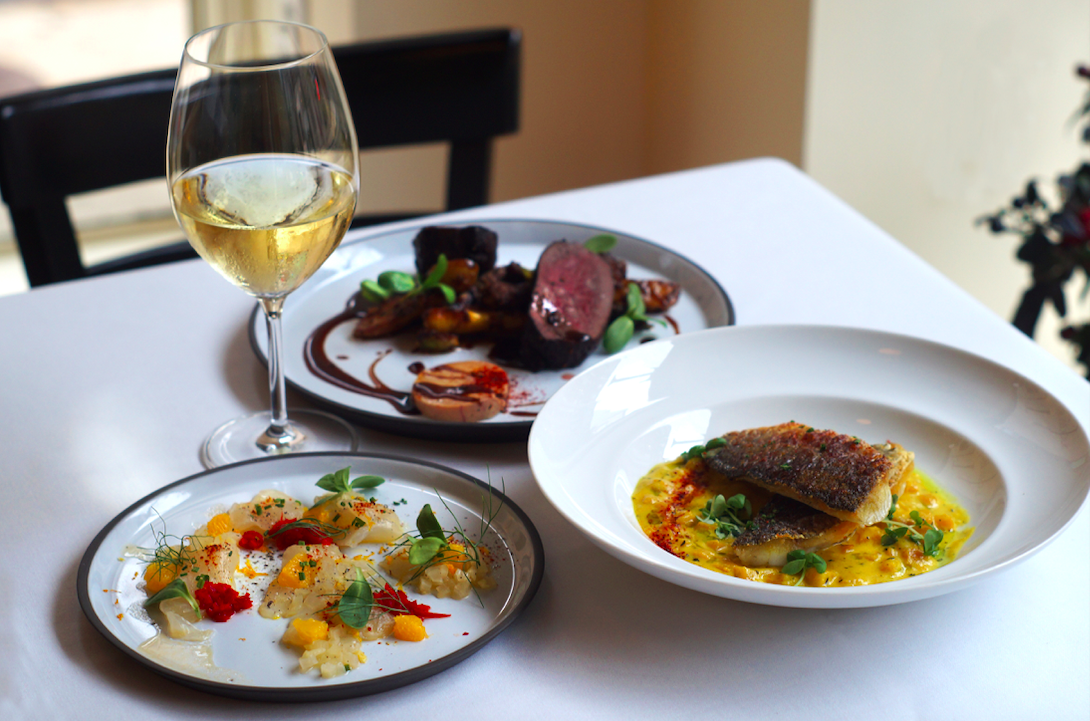 small white plates with food and a glass of white wine