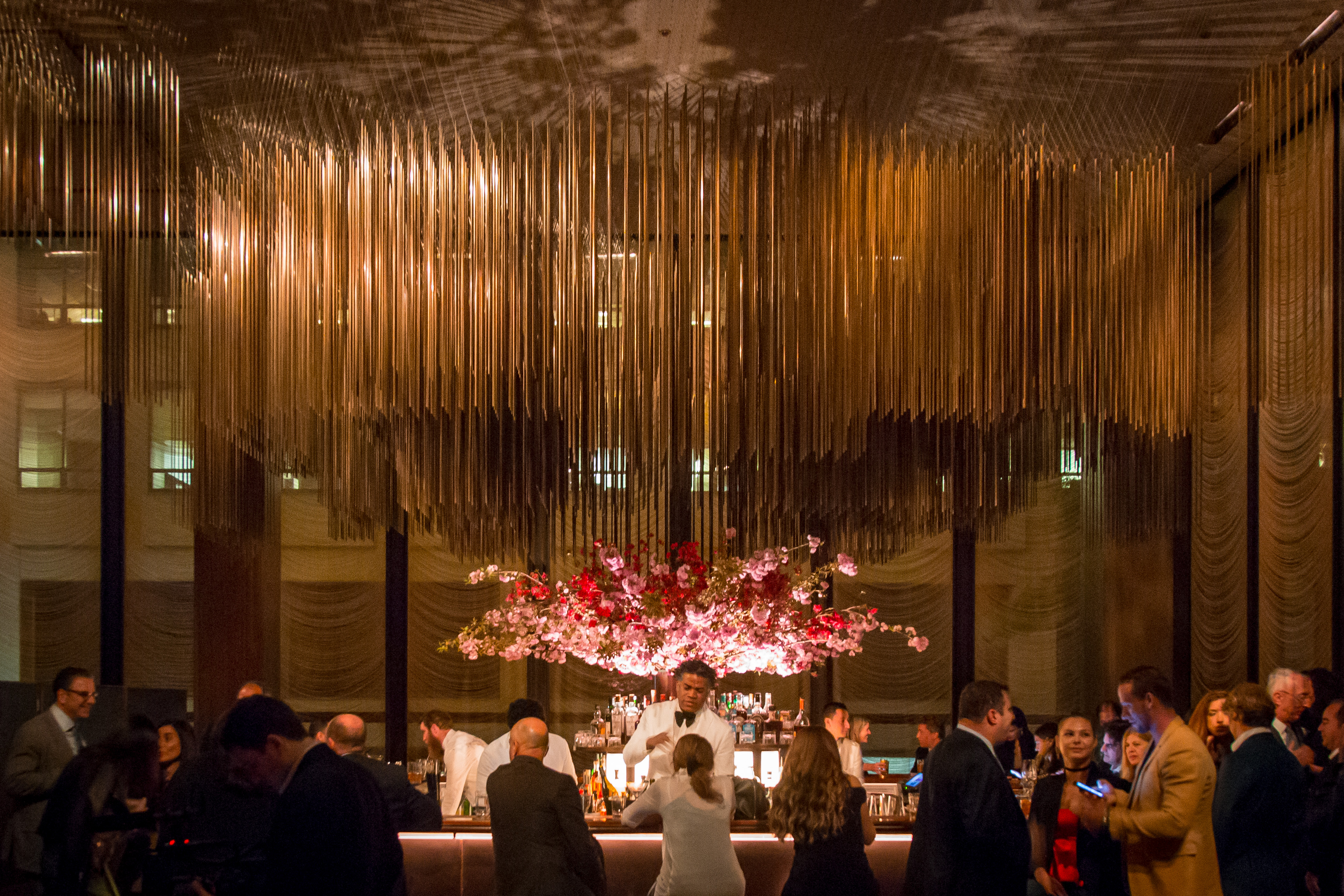 A restaurant bar filled with people. A dramatic chandelier hangs above the bar