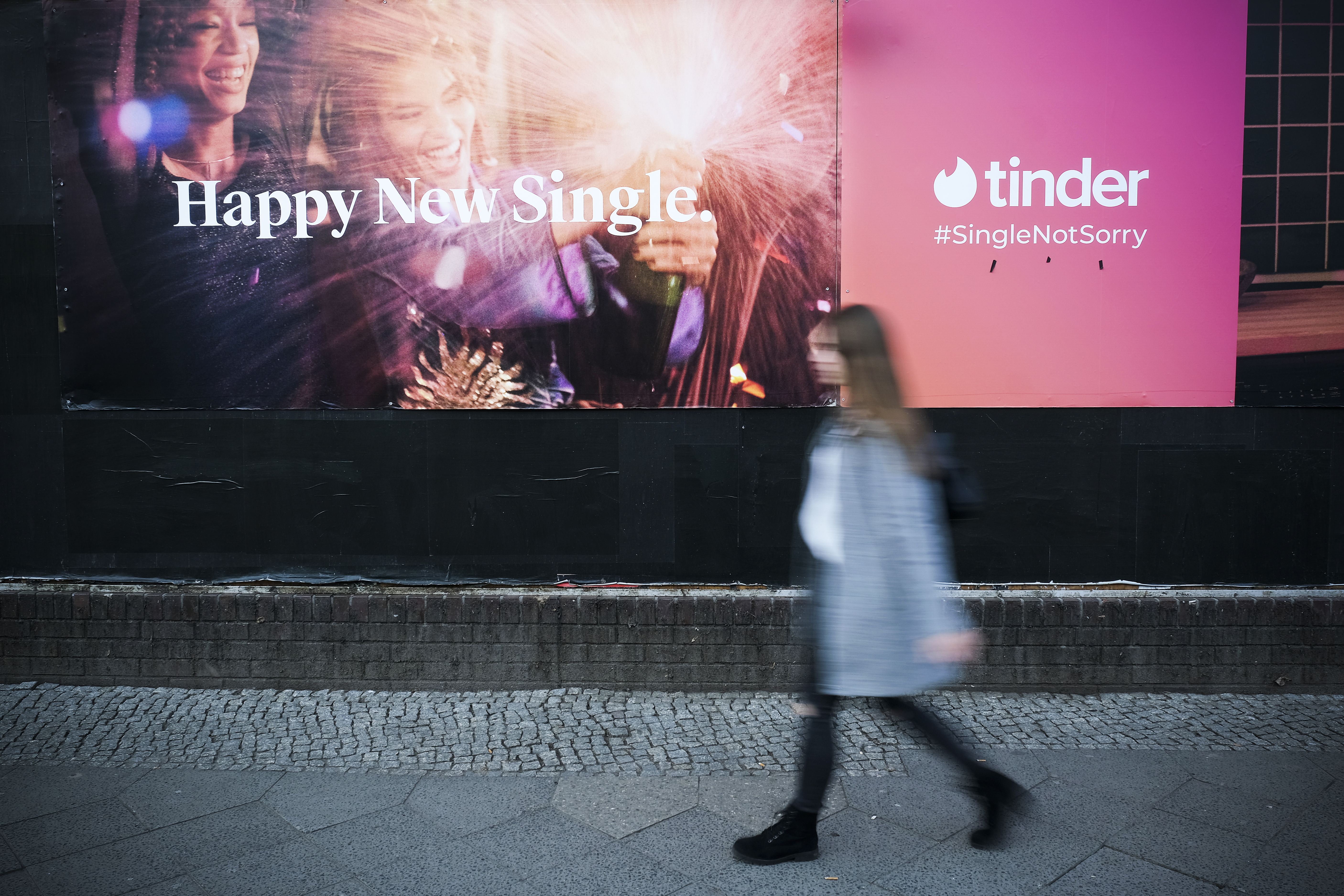 """A woman walking past a billboard advertisement for Tinder that reads, """"Happy New Single."""""""