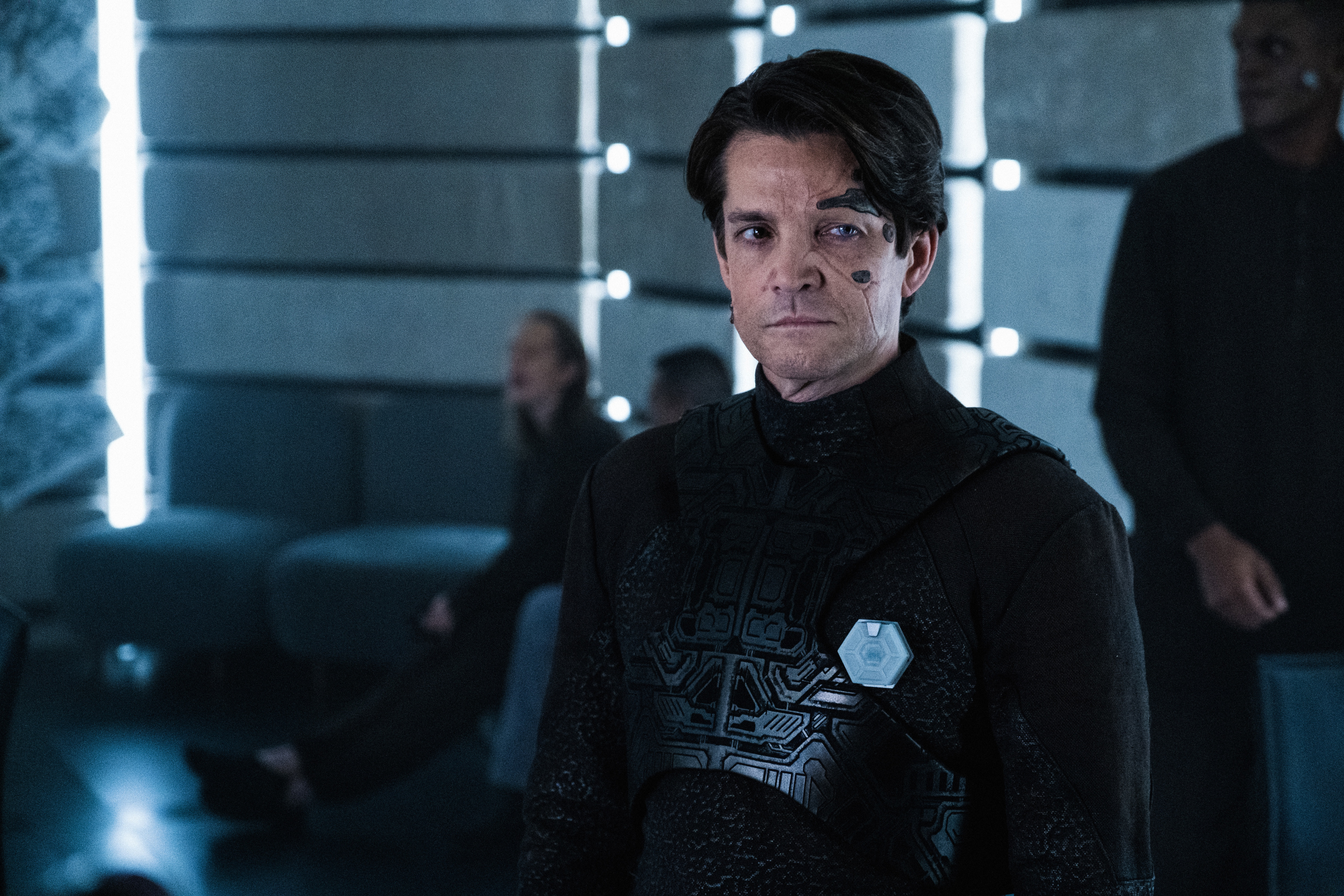 Hugh, a reclaimed Borg dressed in black and bearing metallic face inserts, looks offscreen in Star Trek: Picard.