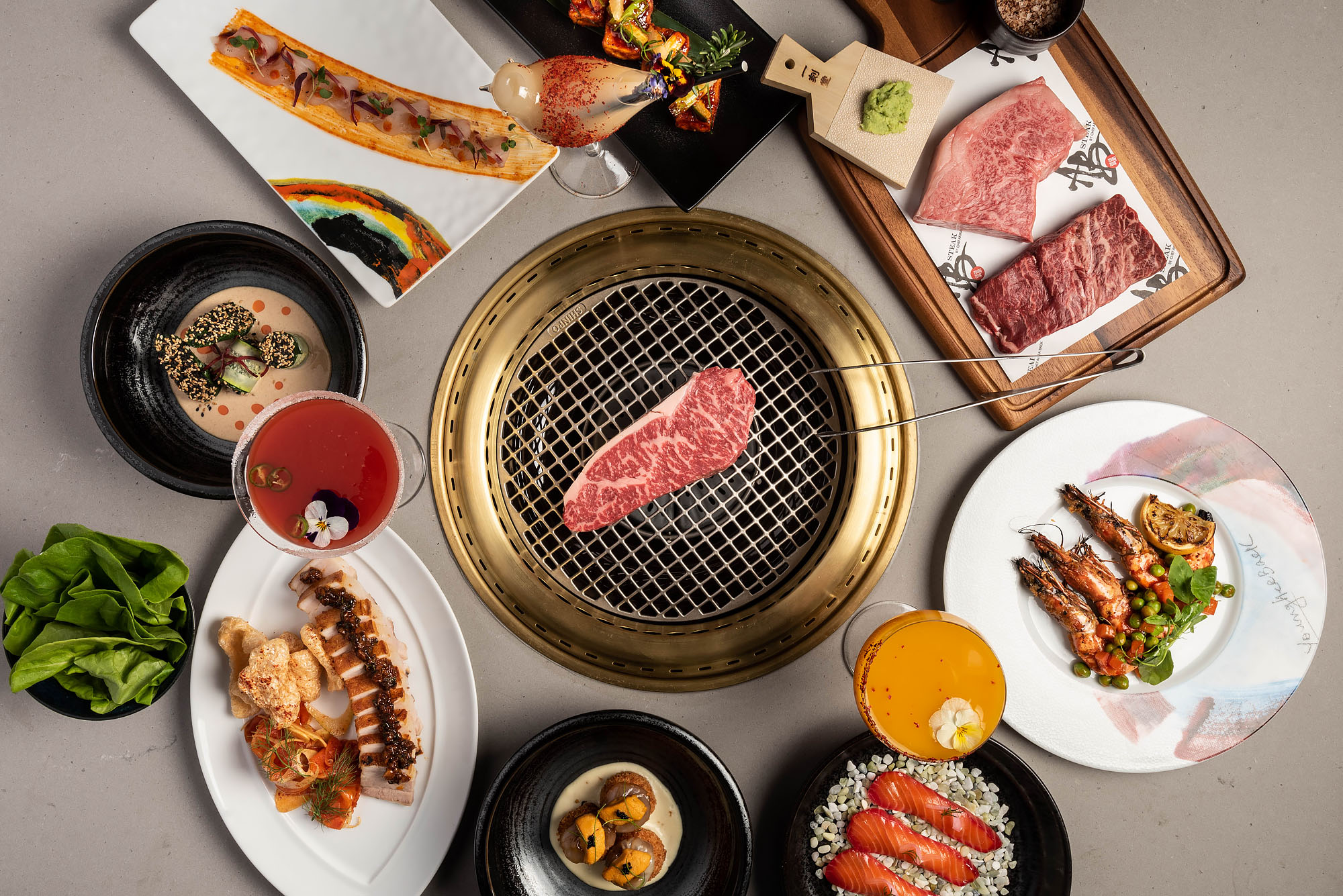 Steak and small plates at ABSteak, Los Angeles around a tabletop grill.