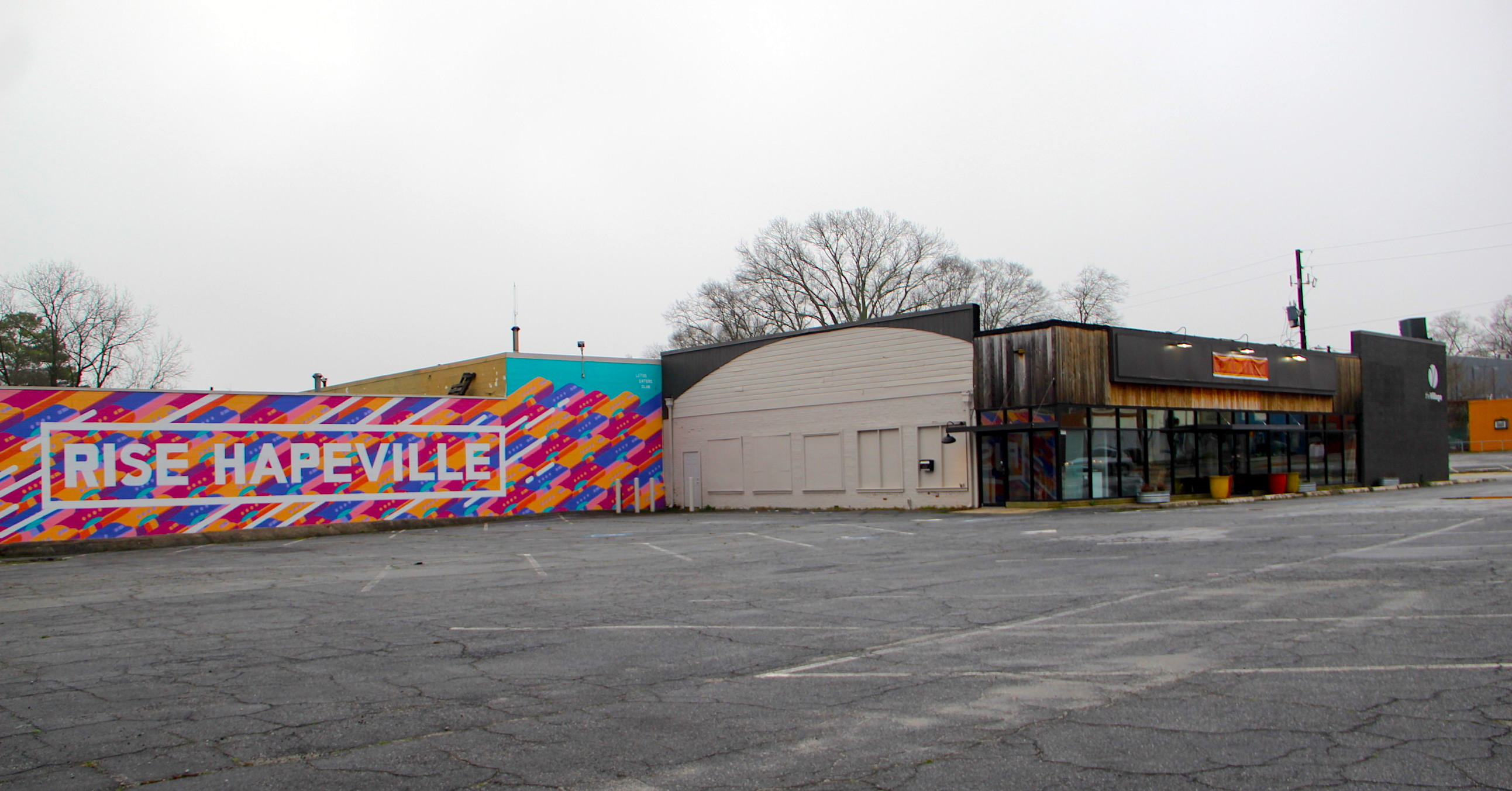 A parking lot with a building at right and colorful wall mural.