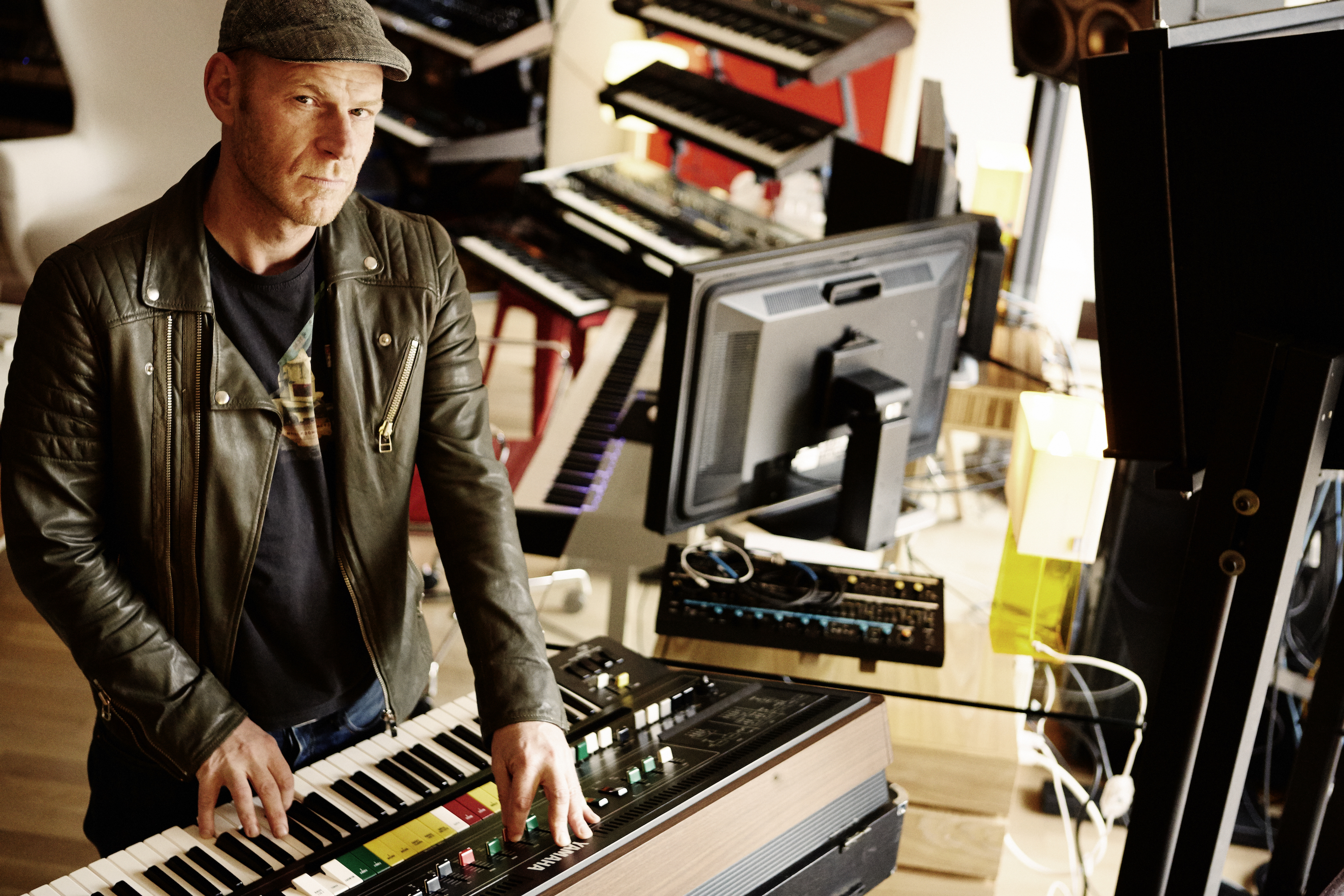 A man wearing a cap and a leather jacket is surrounded by keyboards and synthesizers.