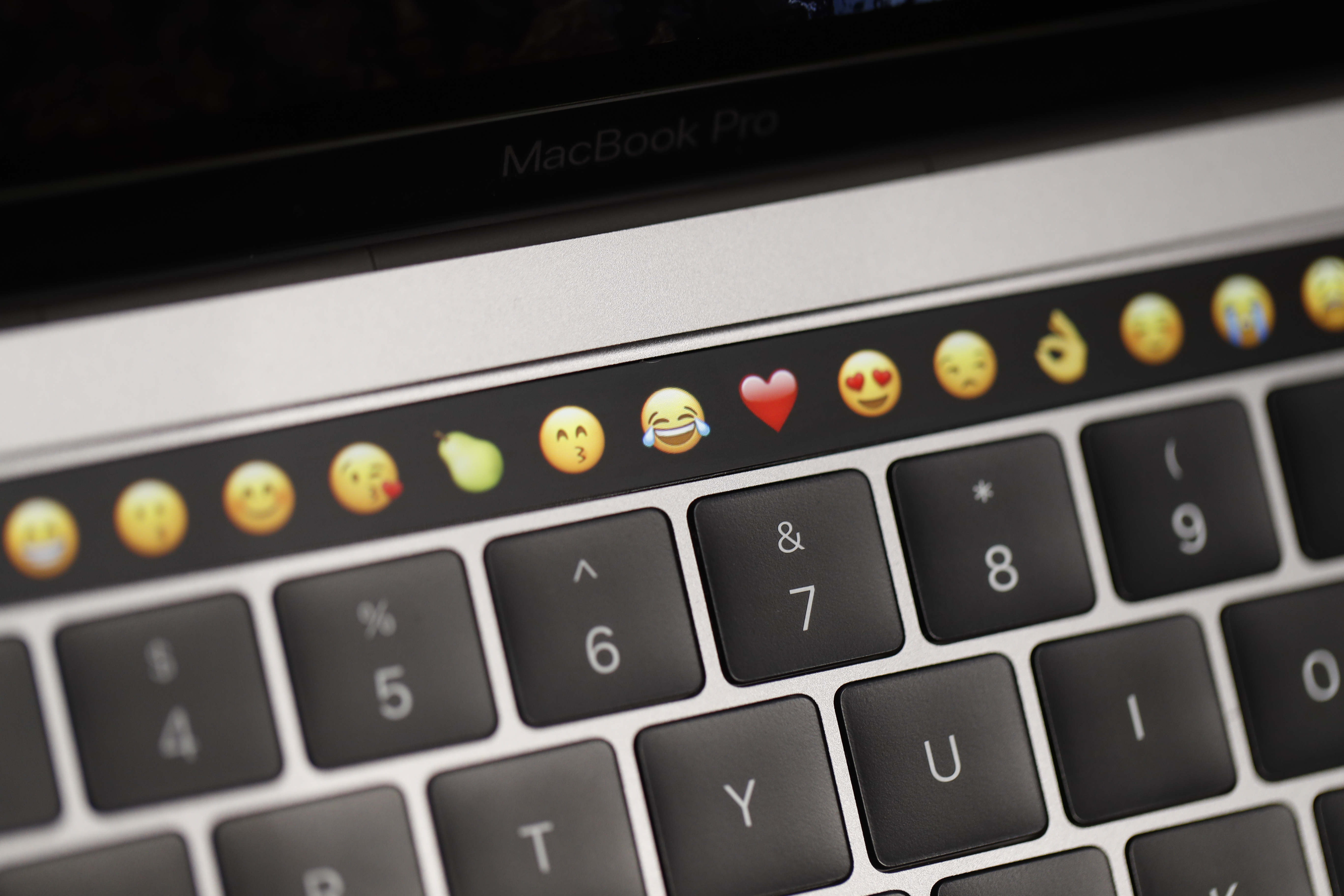 An Apple MacBook Pro's task bar displaying emojis above its keyboard.