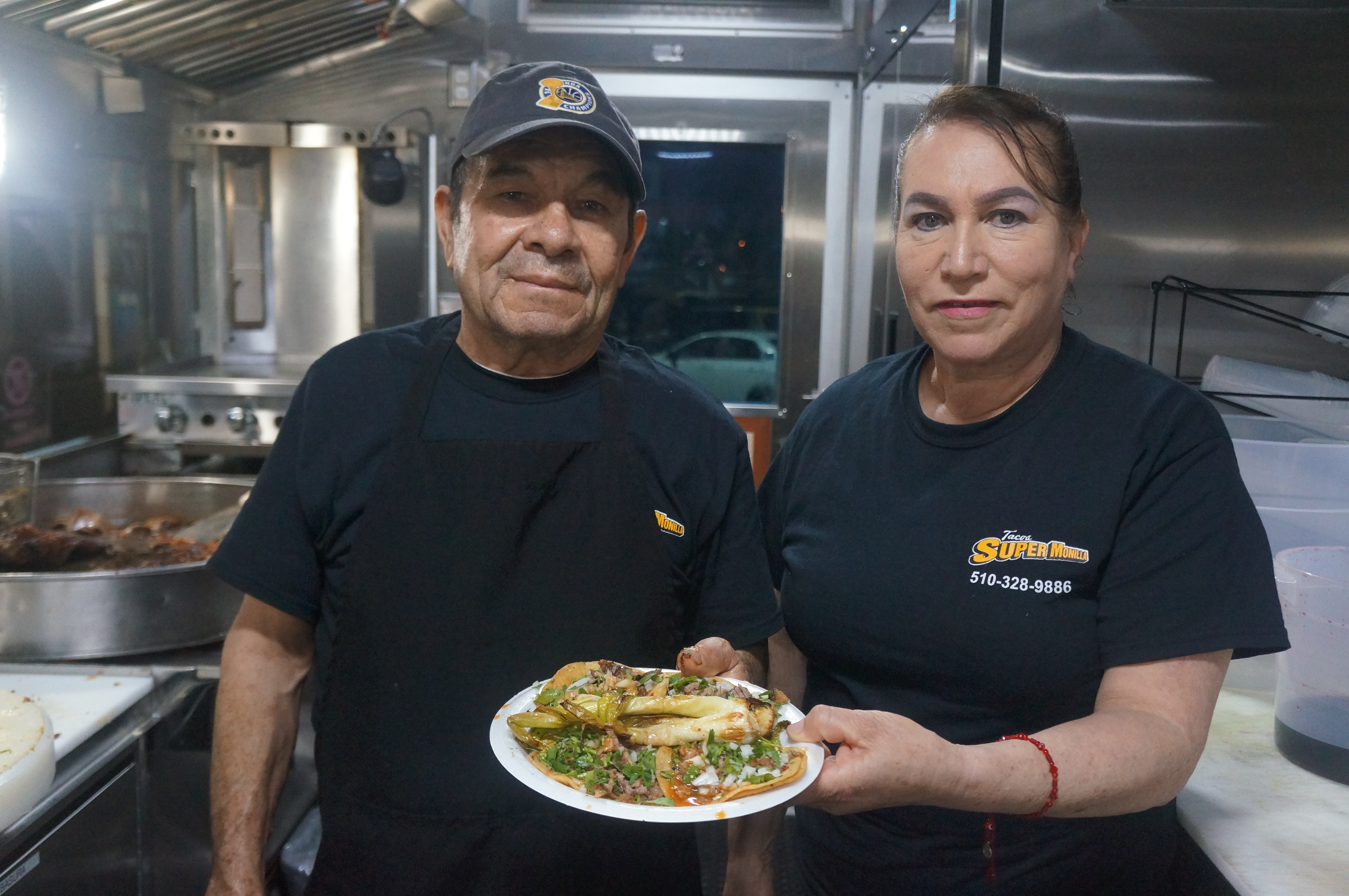 Ramon and Silvia Torres hold a plate of tacos at the Tacos Super Monilla taco truck in Alameda