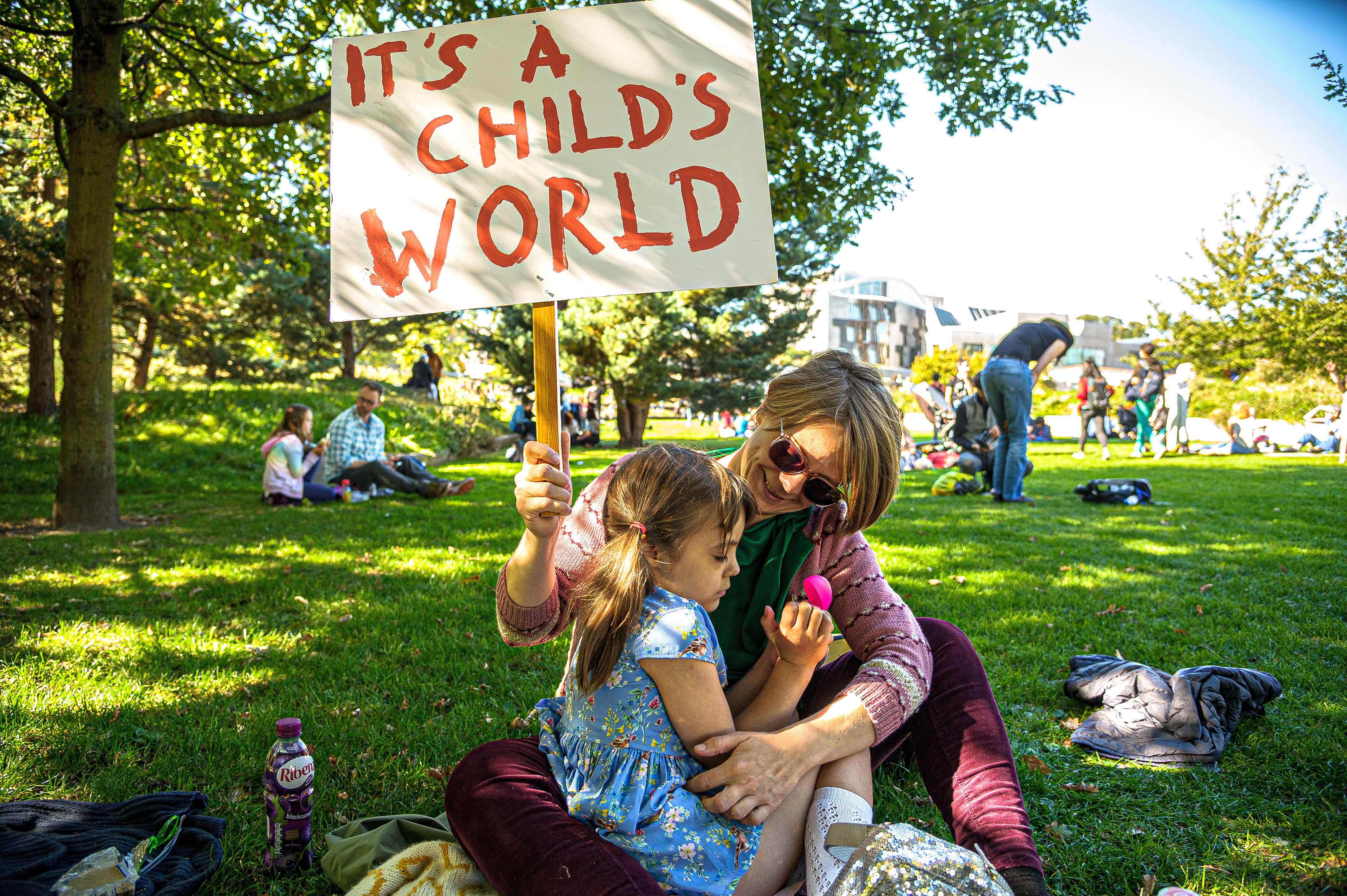 "A mother embracing her daughter holds a placard that says ""It's a child's world"" at the March through Edinburgh, part of the global climate strike movement."
