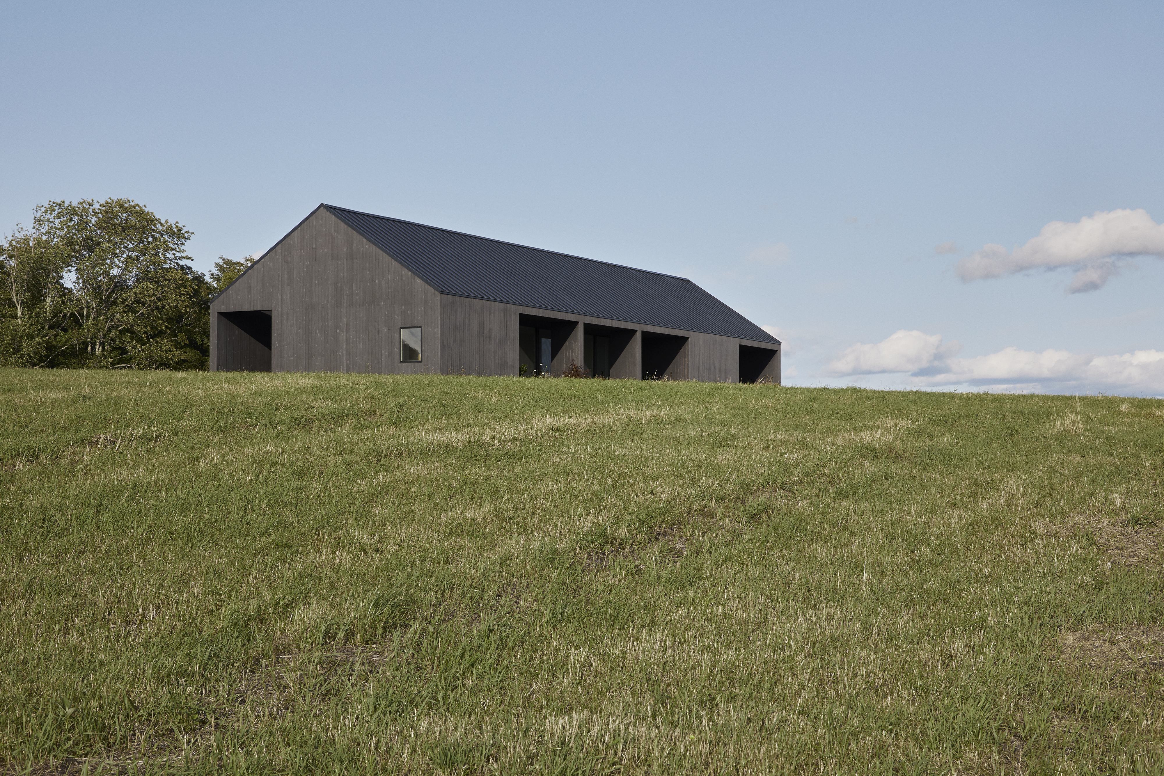 Dark stained wood house on rolling green hill.